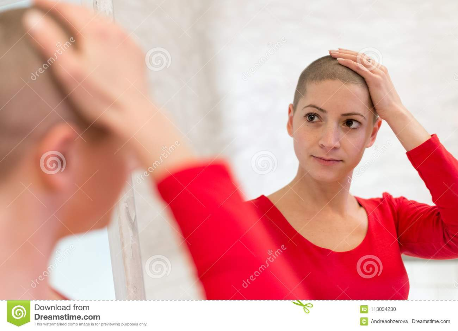 Enfermo de cáncer joven de la hembra adulta que mira en el espejo