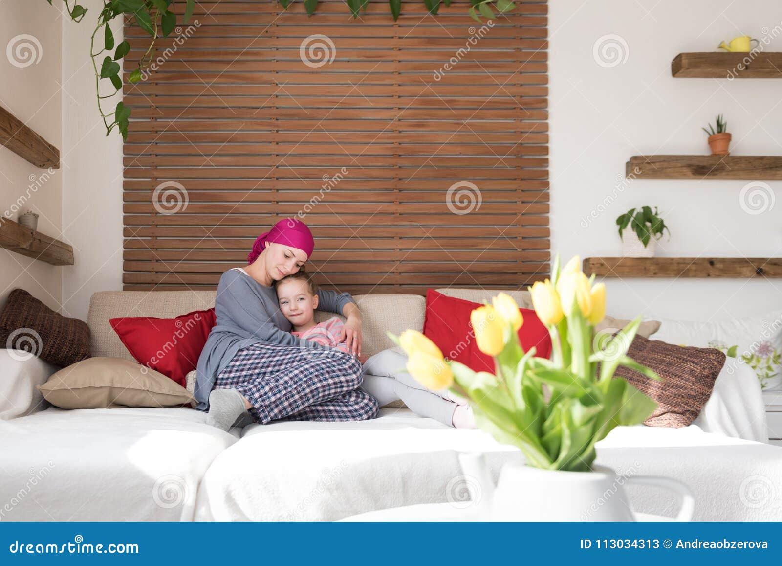 Enfermo de cáncer joven de la hembra adulta que pasa tiempo con su hija en casa, relajándose en el sofá
