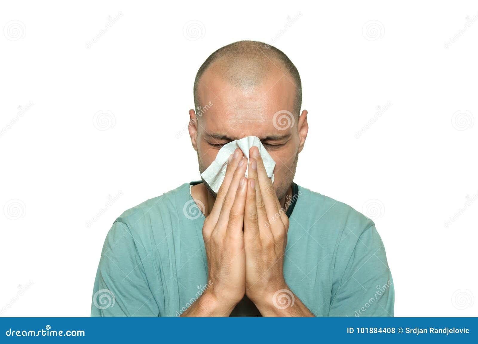 Enfermo del hombre joven de la gripe del frío común que sopla su nariz con el tejido de papel aislado en el fondo blanco