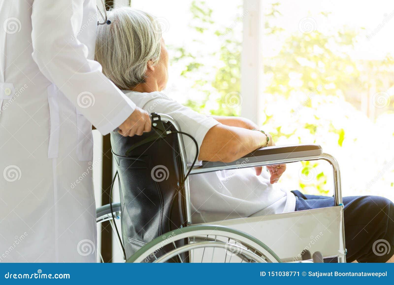 Enfermos de apoio de inquietação do doutor ou da enfermeira, mulher asiática superior na cadeira de rodas, cuidador fêmea que and