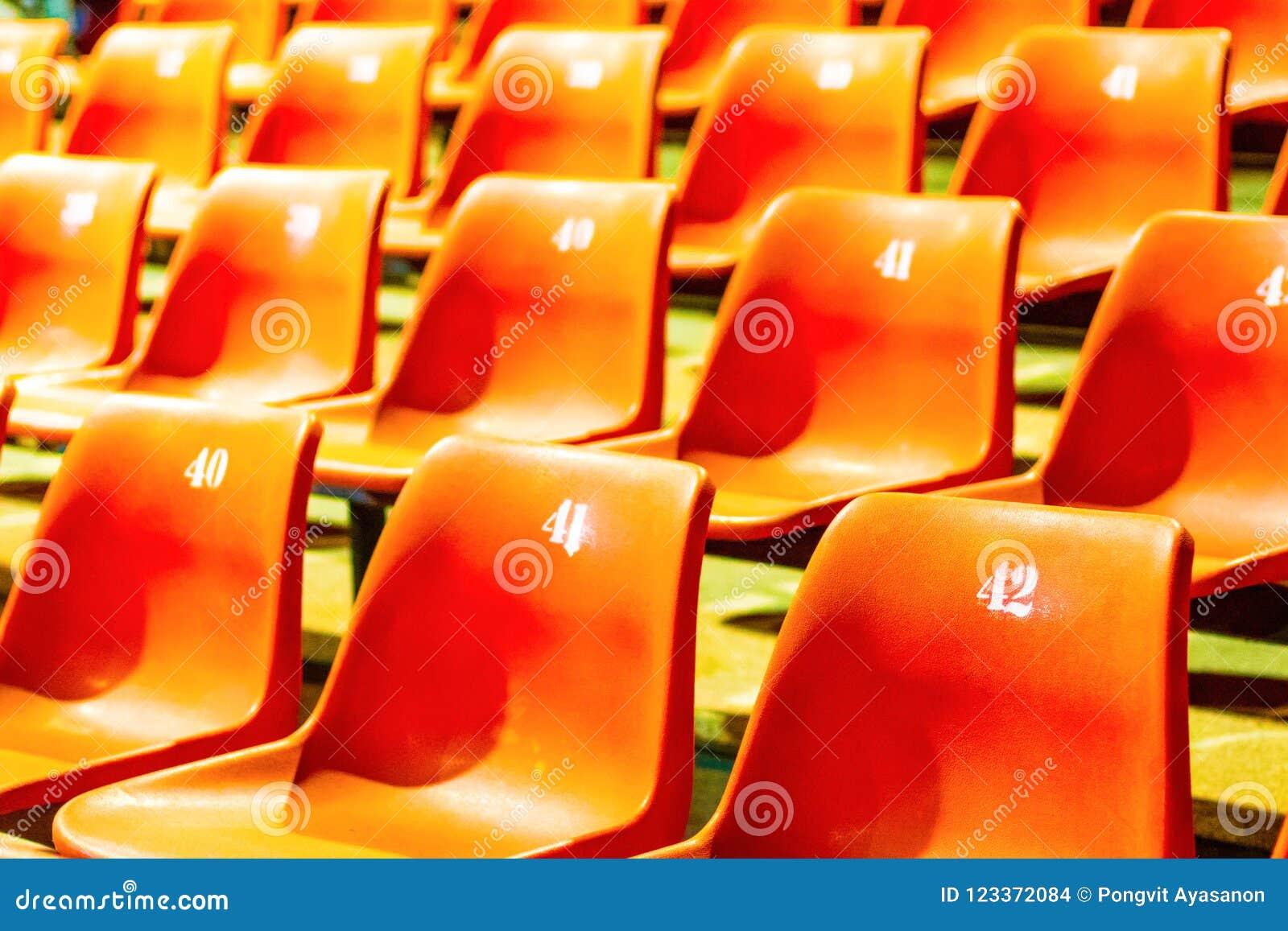 Enfileire a laranja plástica da cadeira com todos os números no grande ro da conferência