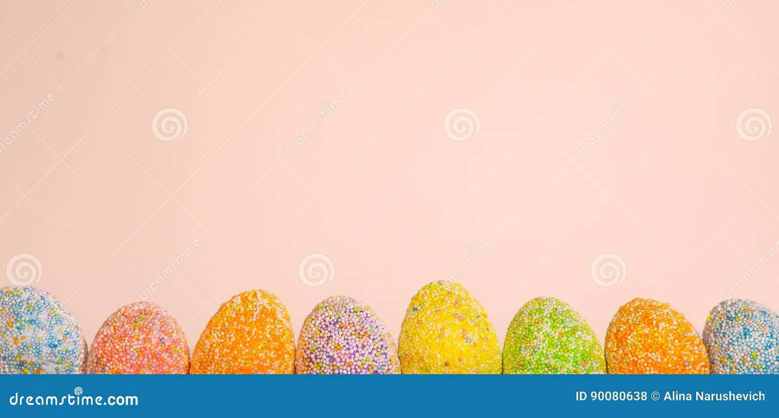 Enfileire ovos da páscoa com luz da mola - fundo cor-de-rosa