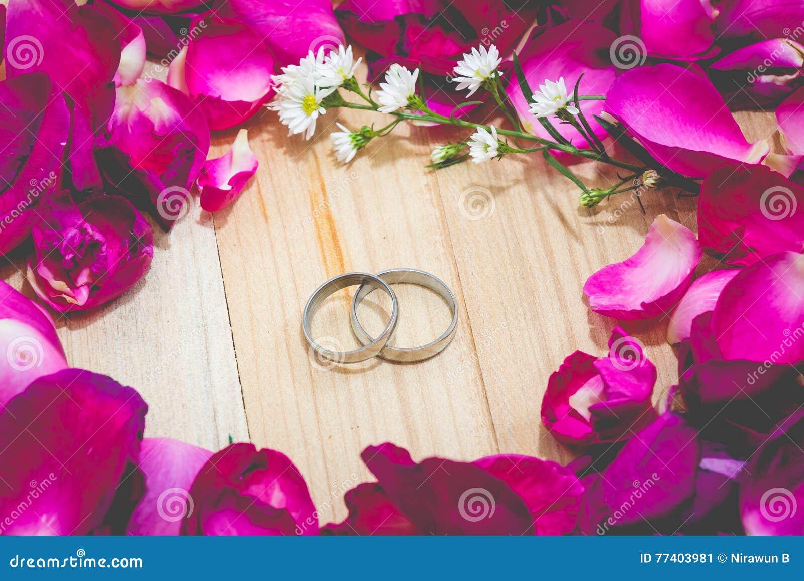 Engagez l anneau parmi le fond en bois dessus mis par rose de pétale