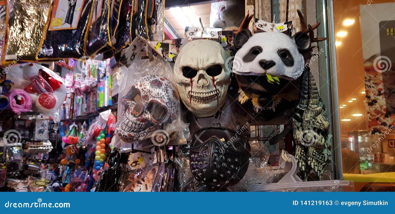 Enge maskers en ander plastic kleurrijk die materiaal voor kinderen voor verkoop in een winkel vóór Joodse purimmaskerade worden