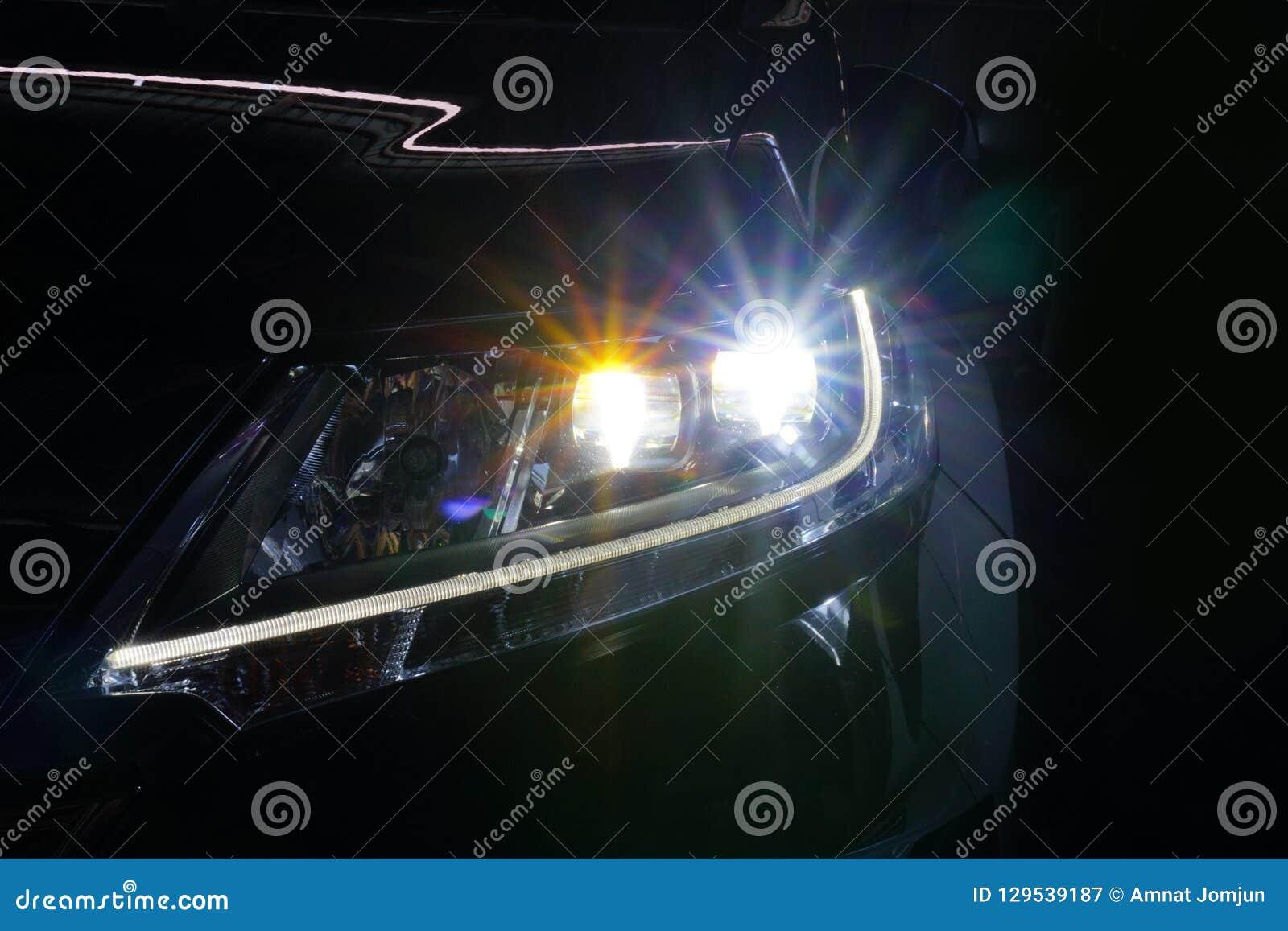 Engel mustert glühende Optiklinse des Xenonscheinwerfers