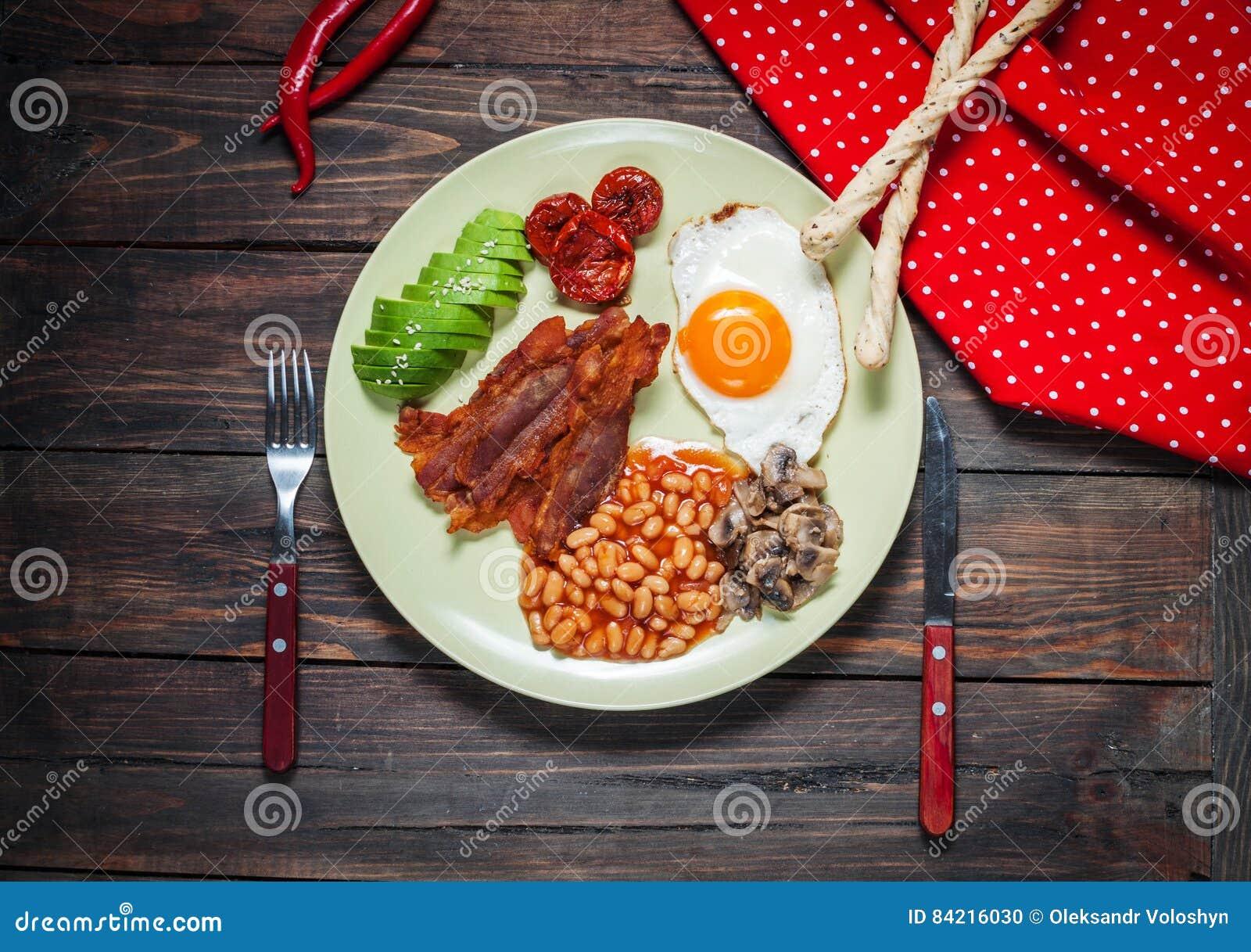 Engelsk frukost av bacon, stekt ägg, bönor, champinjoner, avokado
