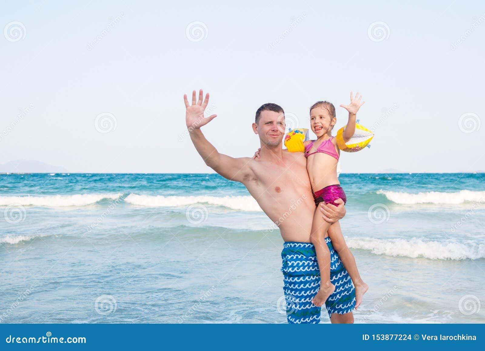 Engendre detener a un beb? alto con la cara feliz cerca del mar