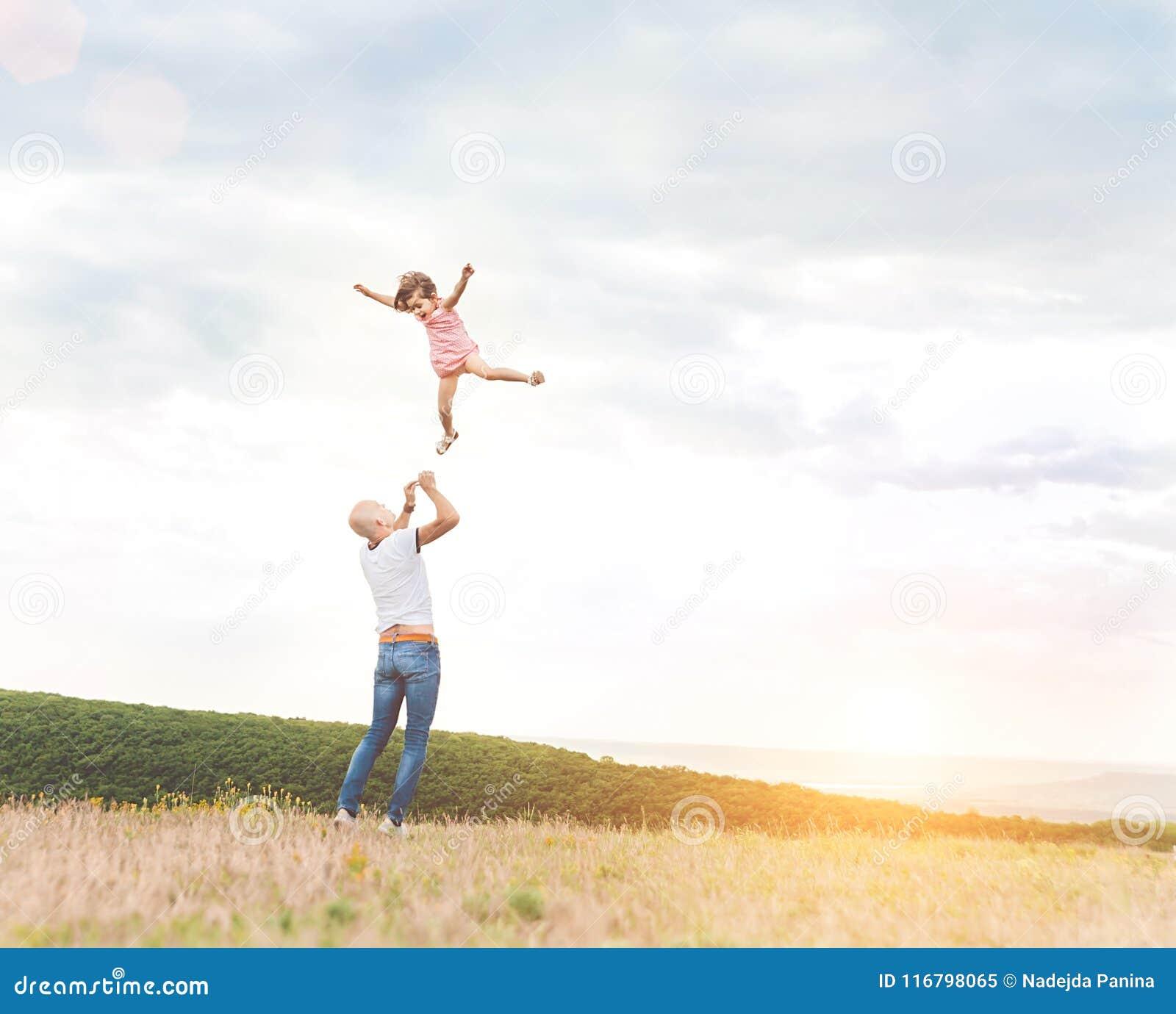 Engendre jugar con su hija en campo soleado