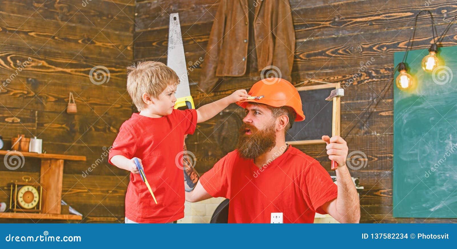 Engendre, parent con la barba en hijo de enseñanza del casco protector para utilizar diversas herramientas en taller de la escuel