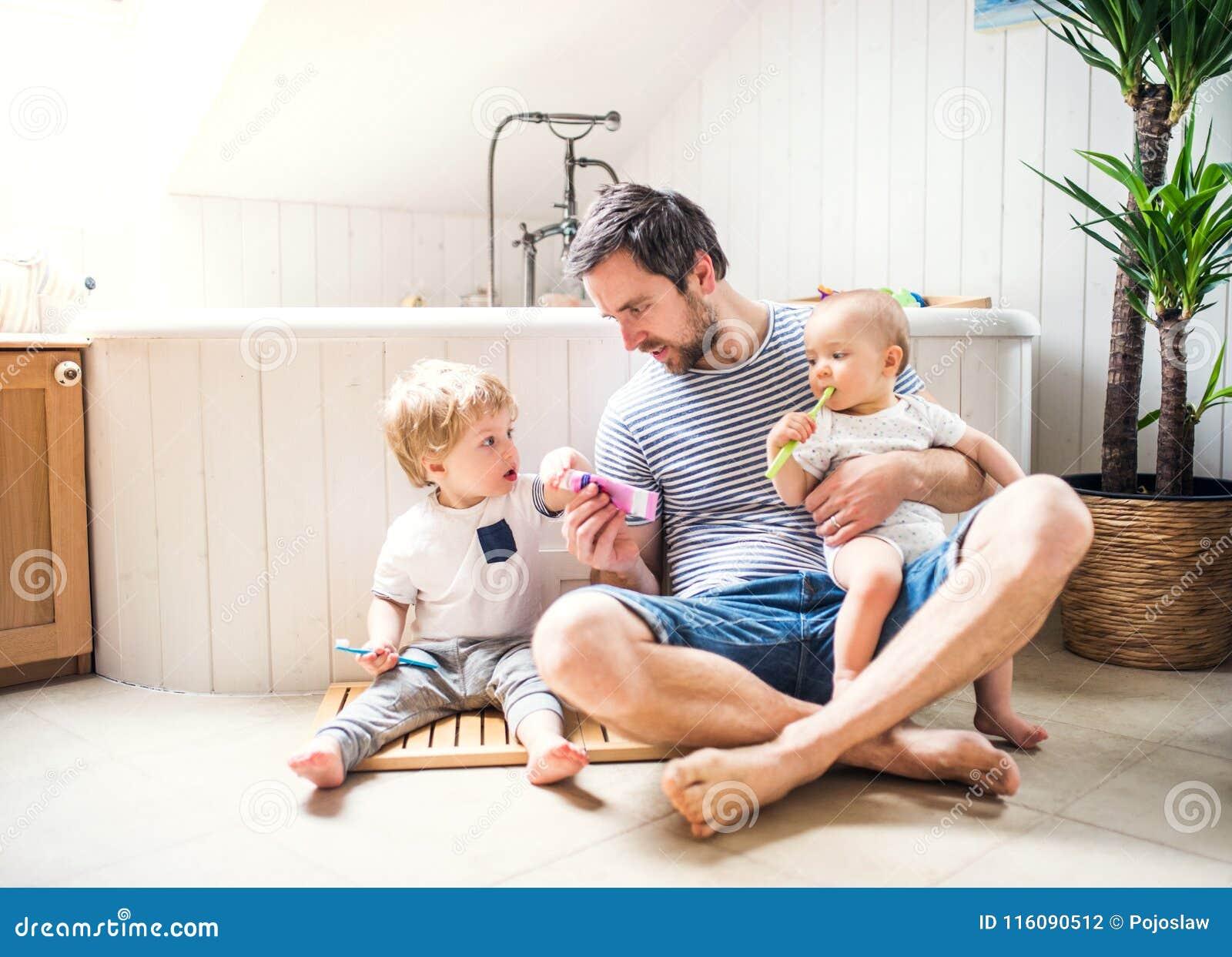 Engendrez avec deux enfants en bas âge brossant des dents dans la salle de bains à la maison