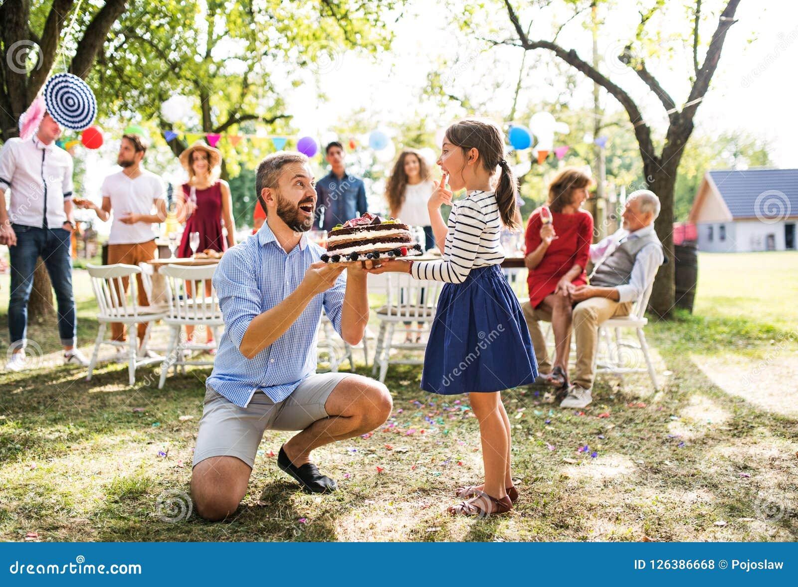 Engendrez donner un gâteau à une petite fille sur une célébration de famille ou une fête d anniversaire