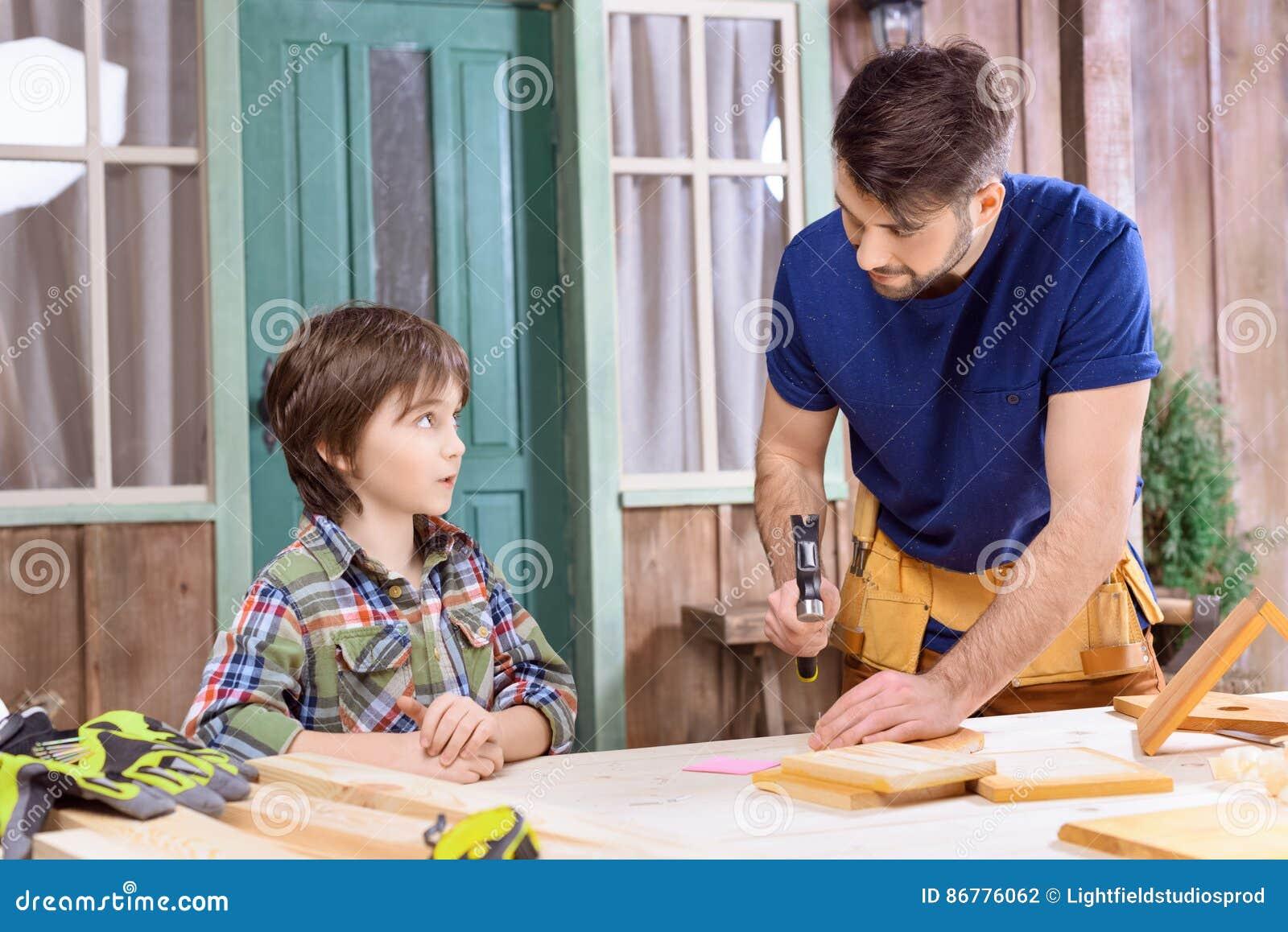 Engendrez le fils concentré de enseignement comment à marteler le clou dans la planche en bois