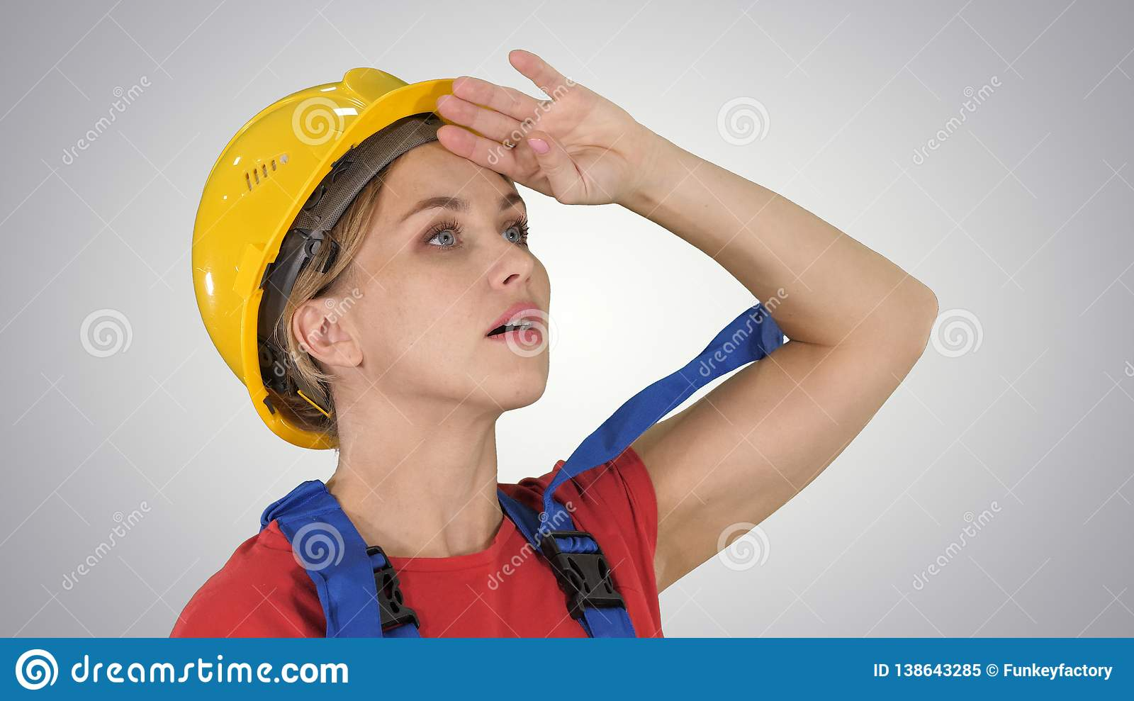 Engineer construction worker woman fascinated by the scale of construction on gradient background.