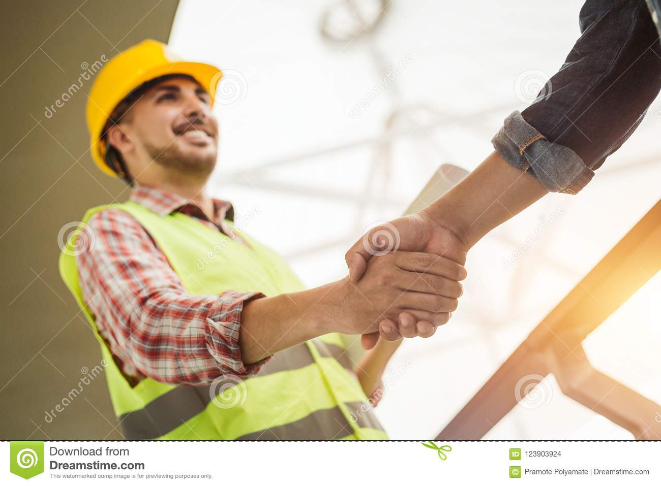 Engineer construction workers in protective helmets and vests ar