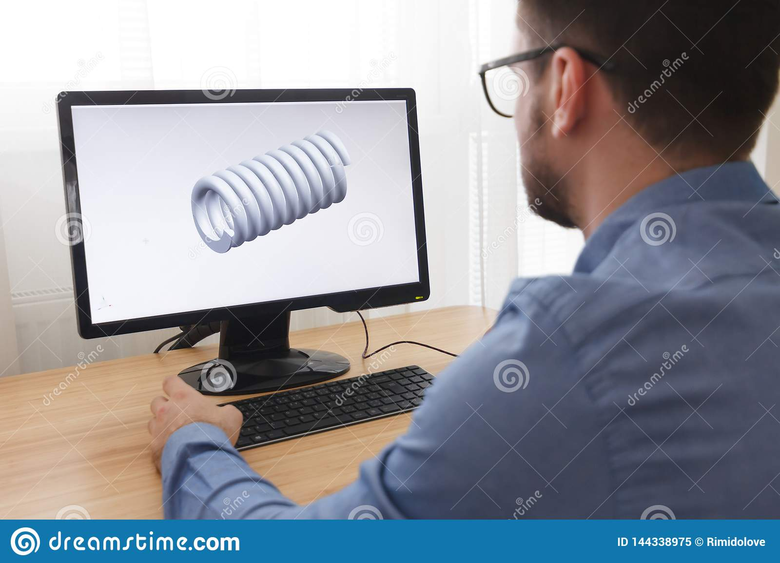 Engineer, Constructor, Designer in Glasses Working on a Personal Computer. He is Creating, Designing a New 3D Model of Mechanical