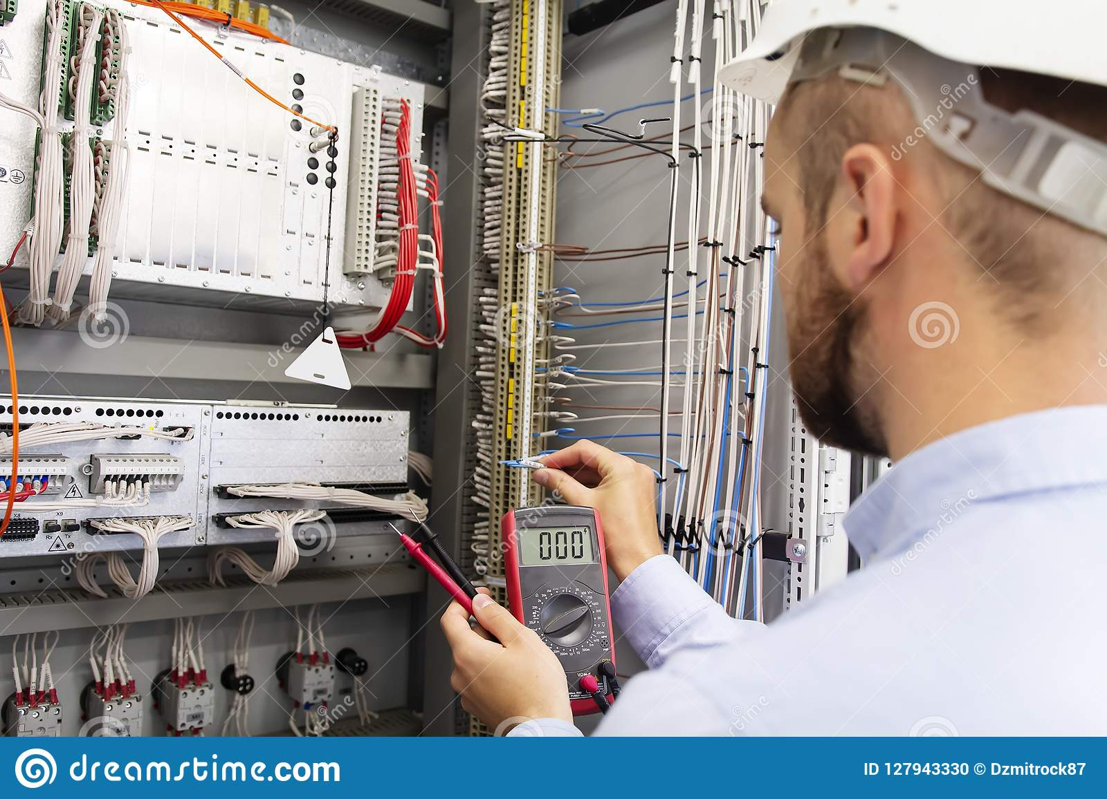 maintenance of electrical panel  worker in helmet in power supply cabinet   service man is testing automation fuse box
