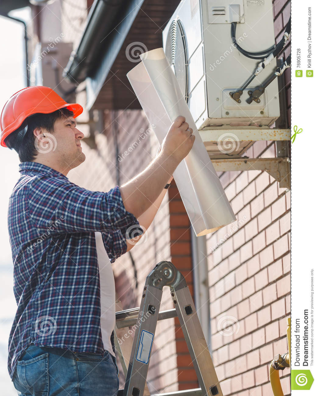 Engineer in hardhat looking in plan of air conditioning system