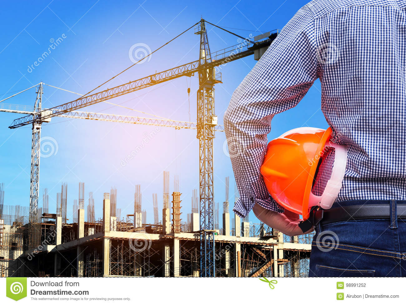 Engineer holding yellow safety helmet in building construction site with crane