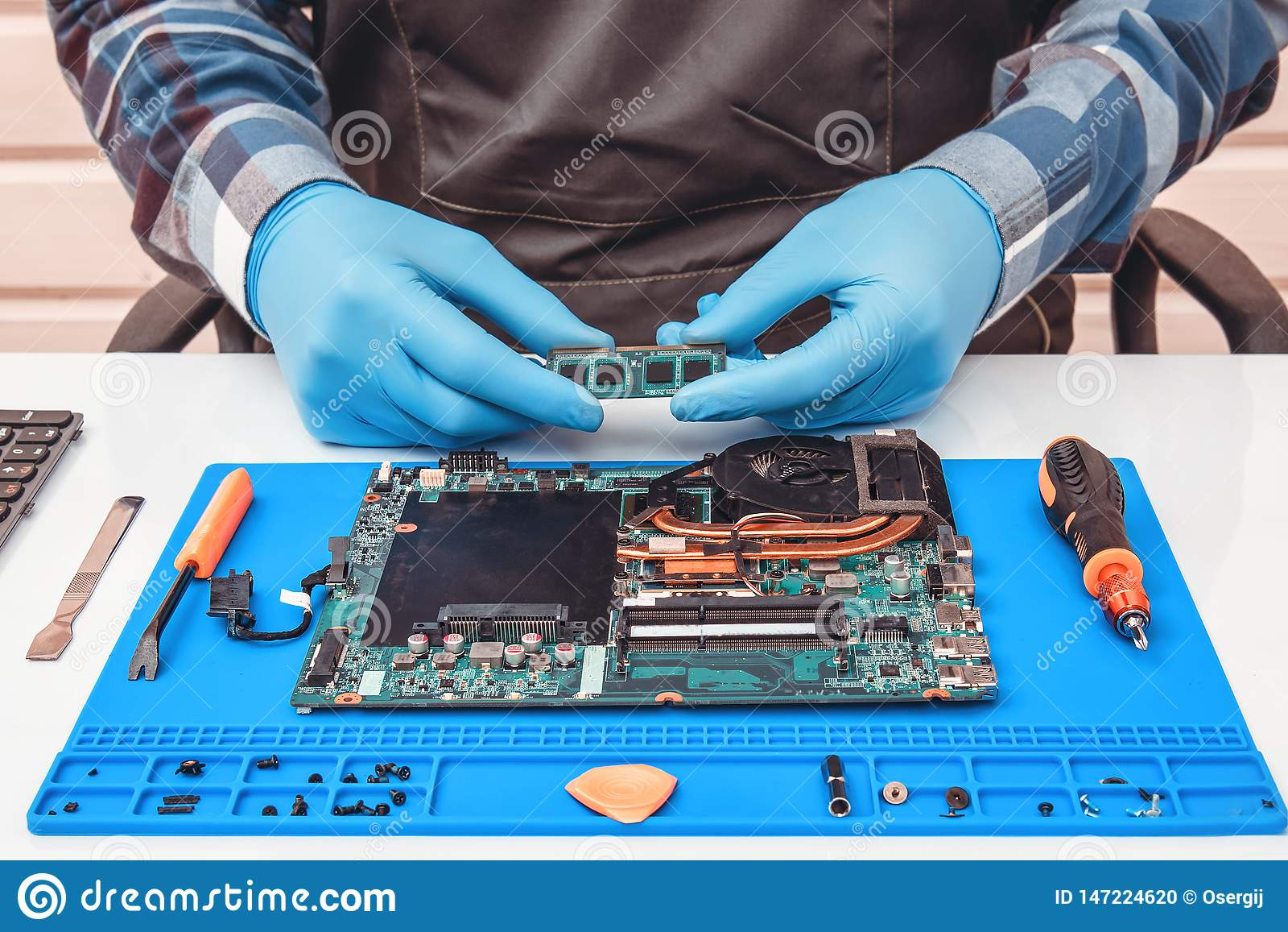 Engineer makes dismantling of RAM for disassembling and repairing a laptop