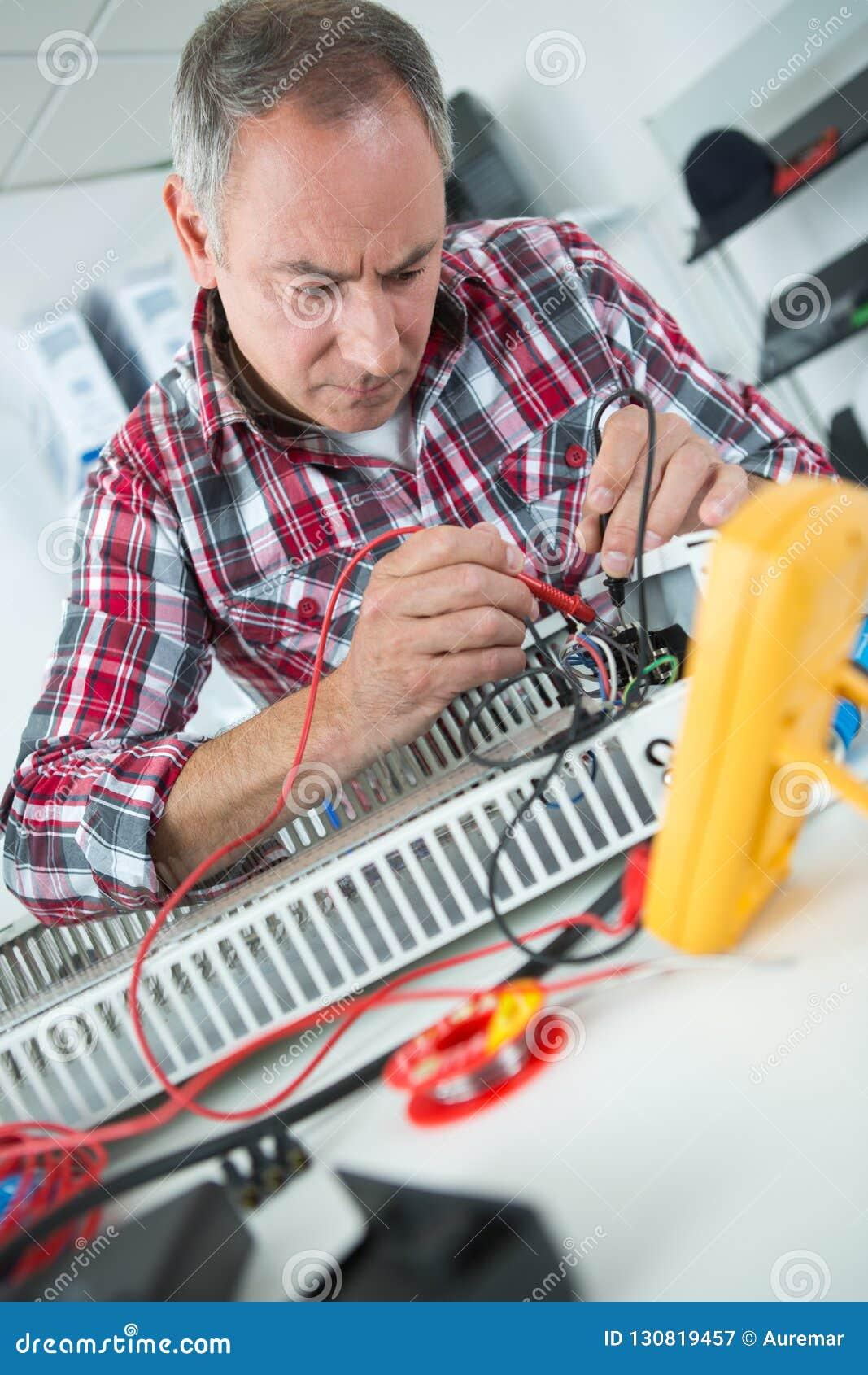 Engineer measuring multimeter panel board