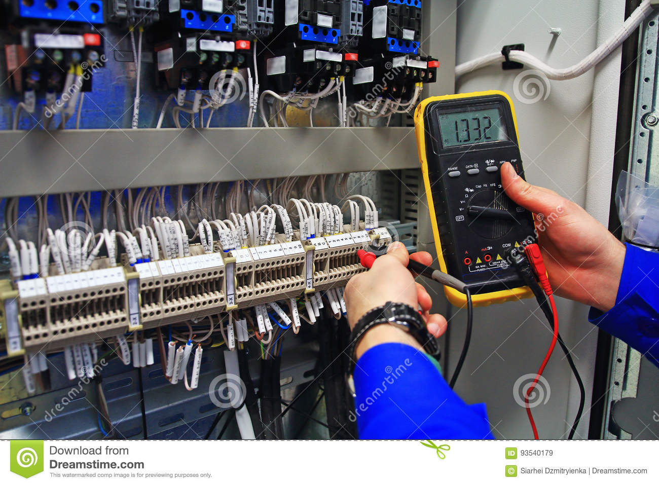 Engineer tests industrial electrical circuits with a multimeter in the control terminal box