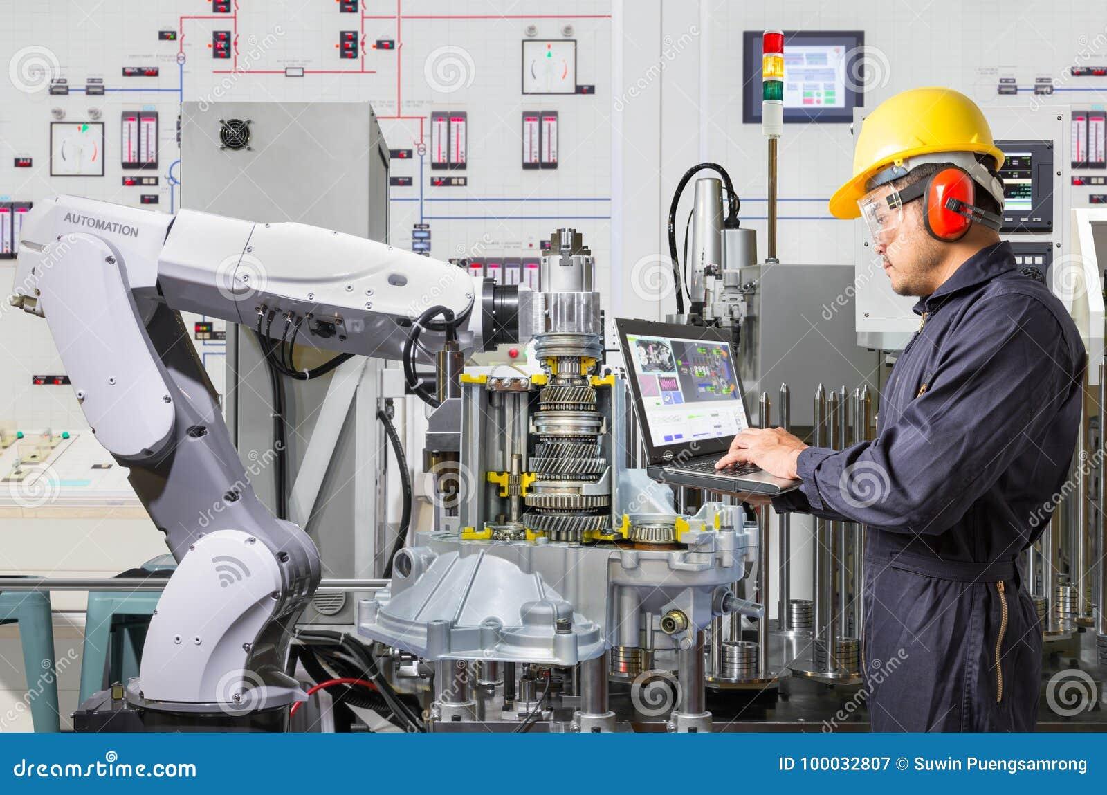 Engineer using laptop computer for maintenance robotic industry