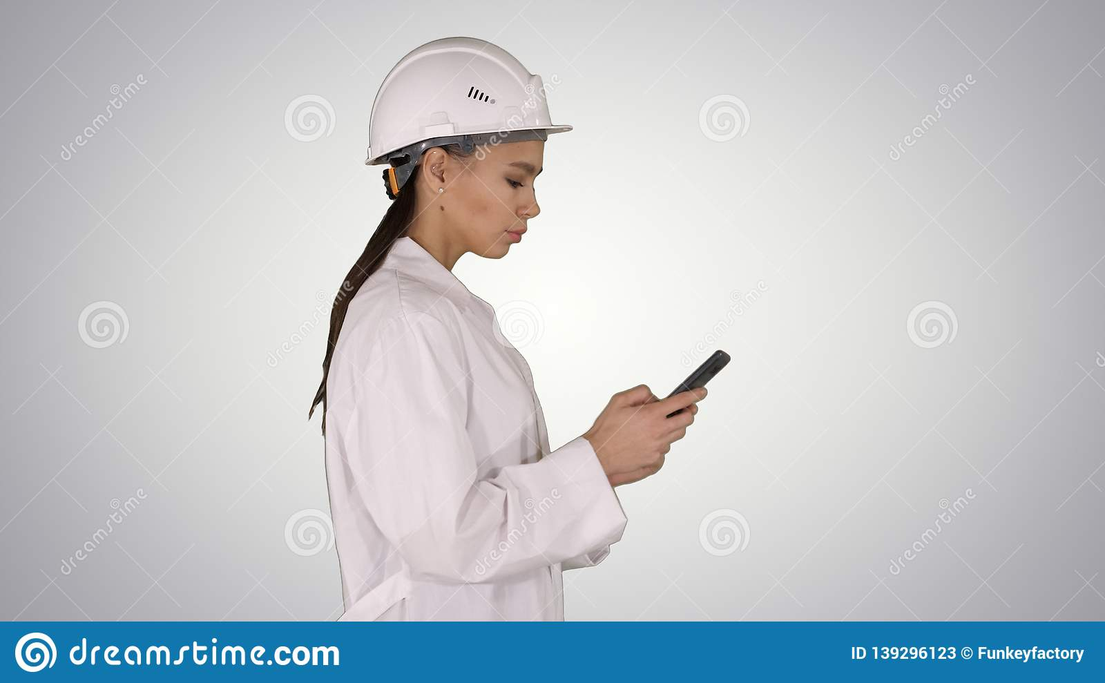 Engineer using mobile phone texting while walking on gradient background.
