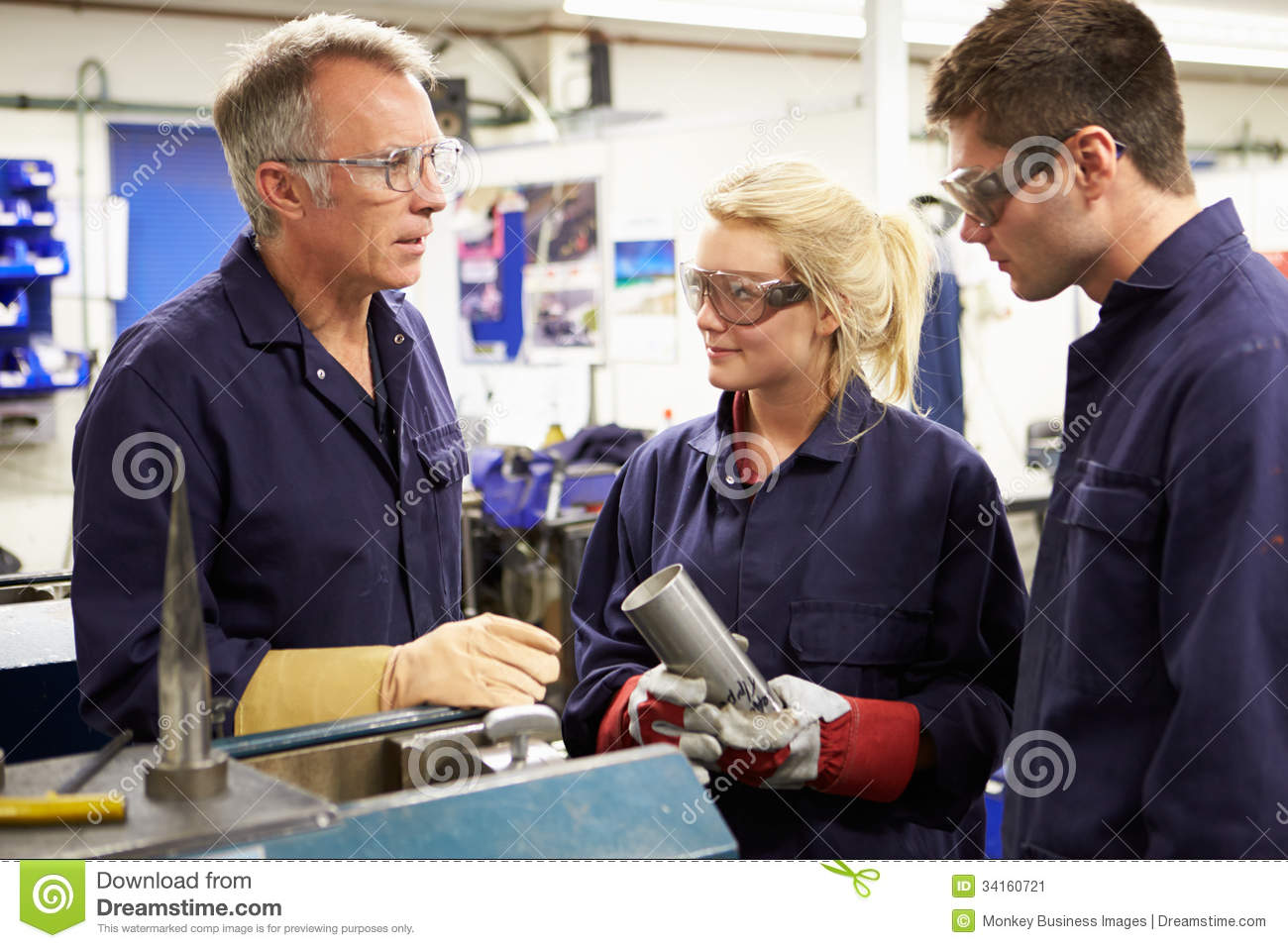Engineer Working With Apprentices On Factory Floor