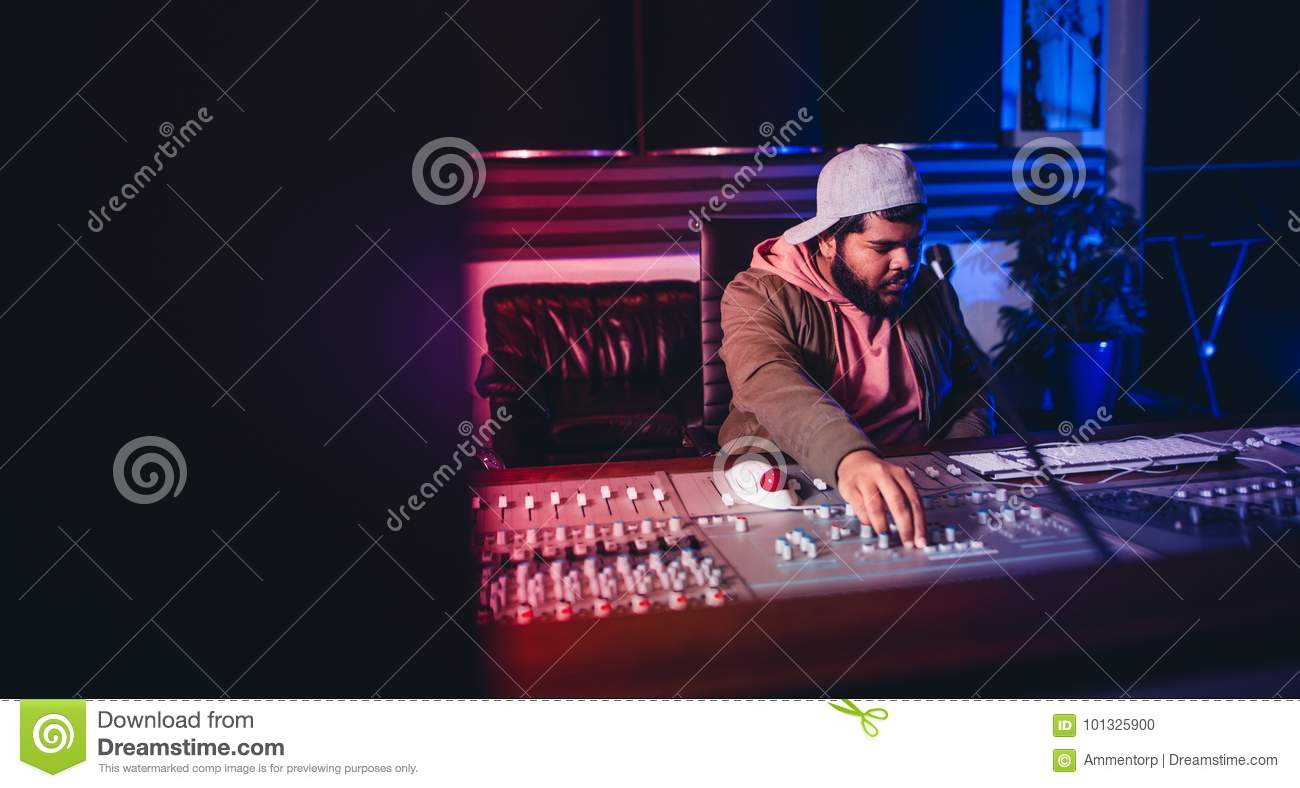 Engineer working on sound mixing desk in recording studio