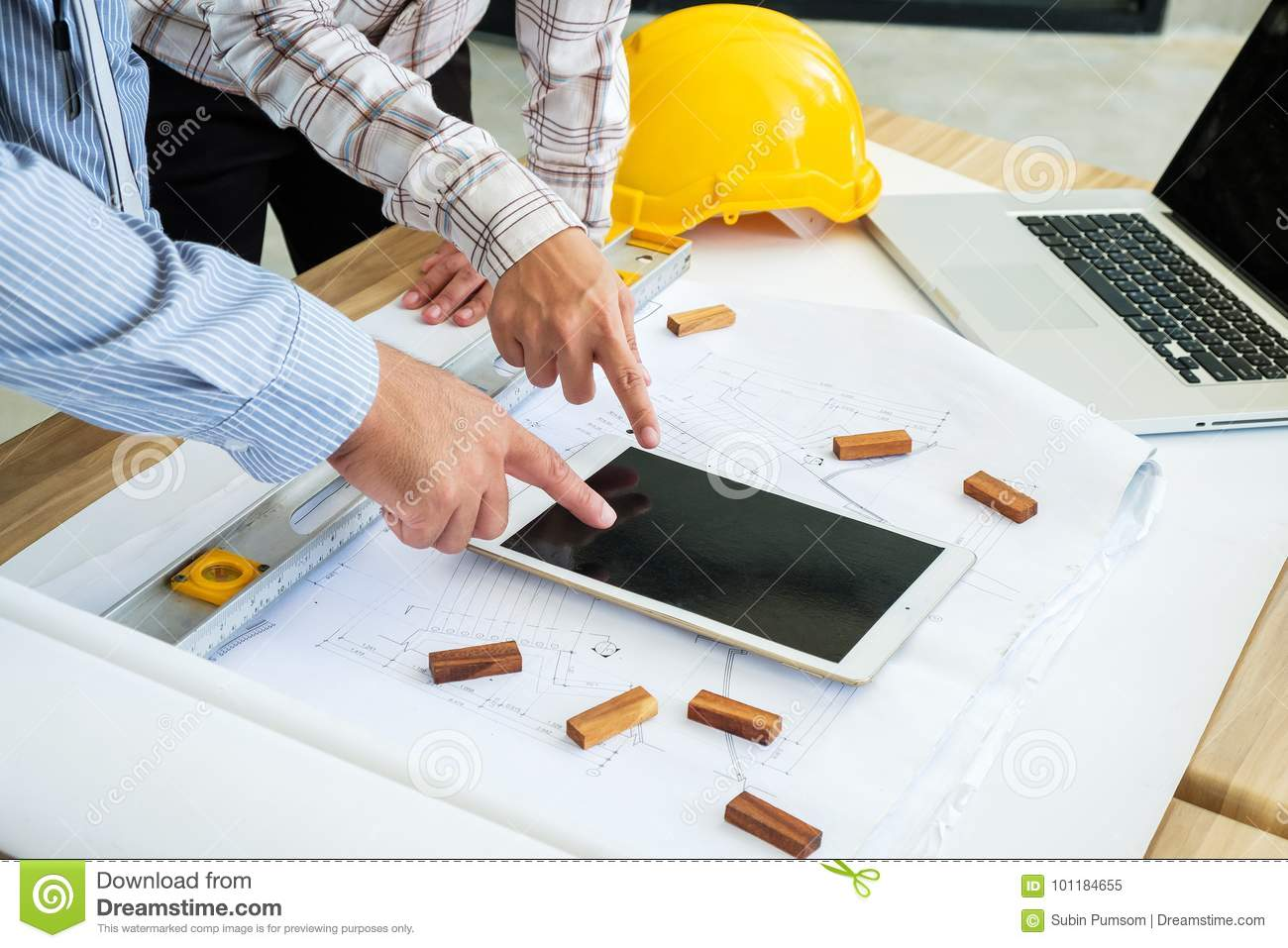 Engineering is looking tablet on a blueprint. To prepare for fie