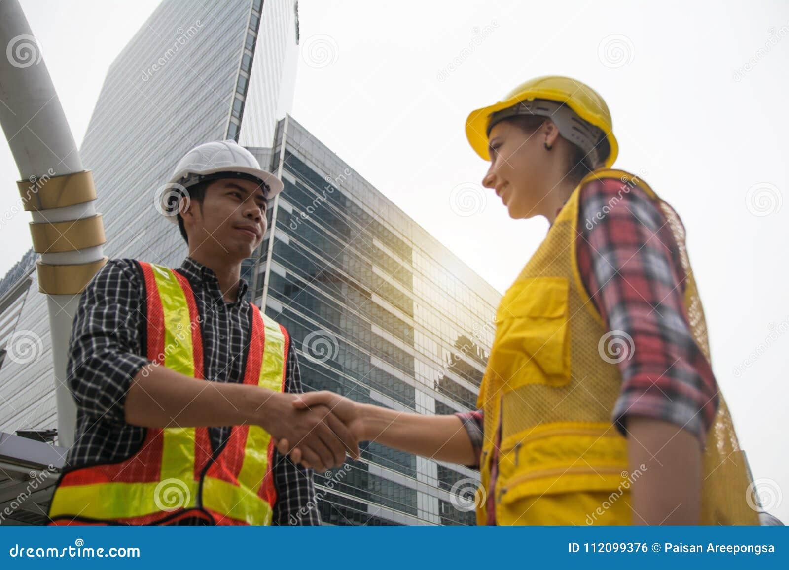 Engineerss трясет руки для того чтобы отпраздновать день успеха