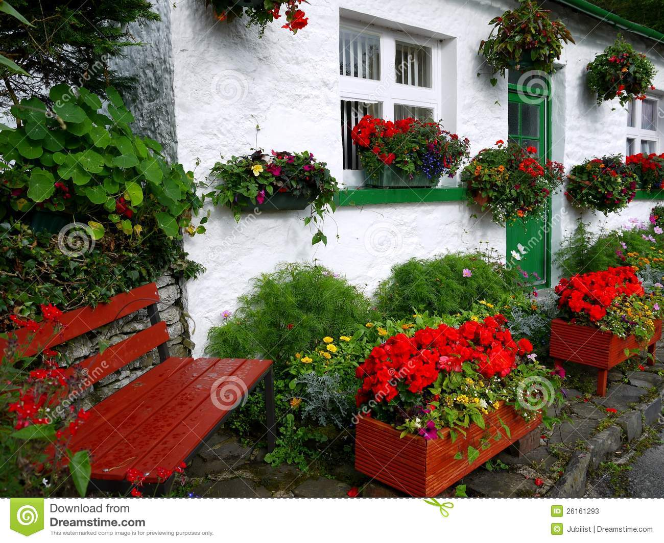England White Cottage With Flowers And Bench
