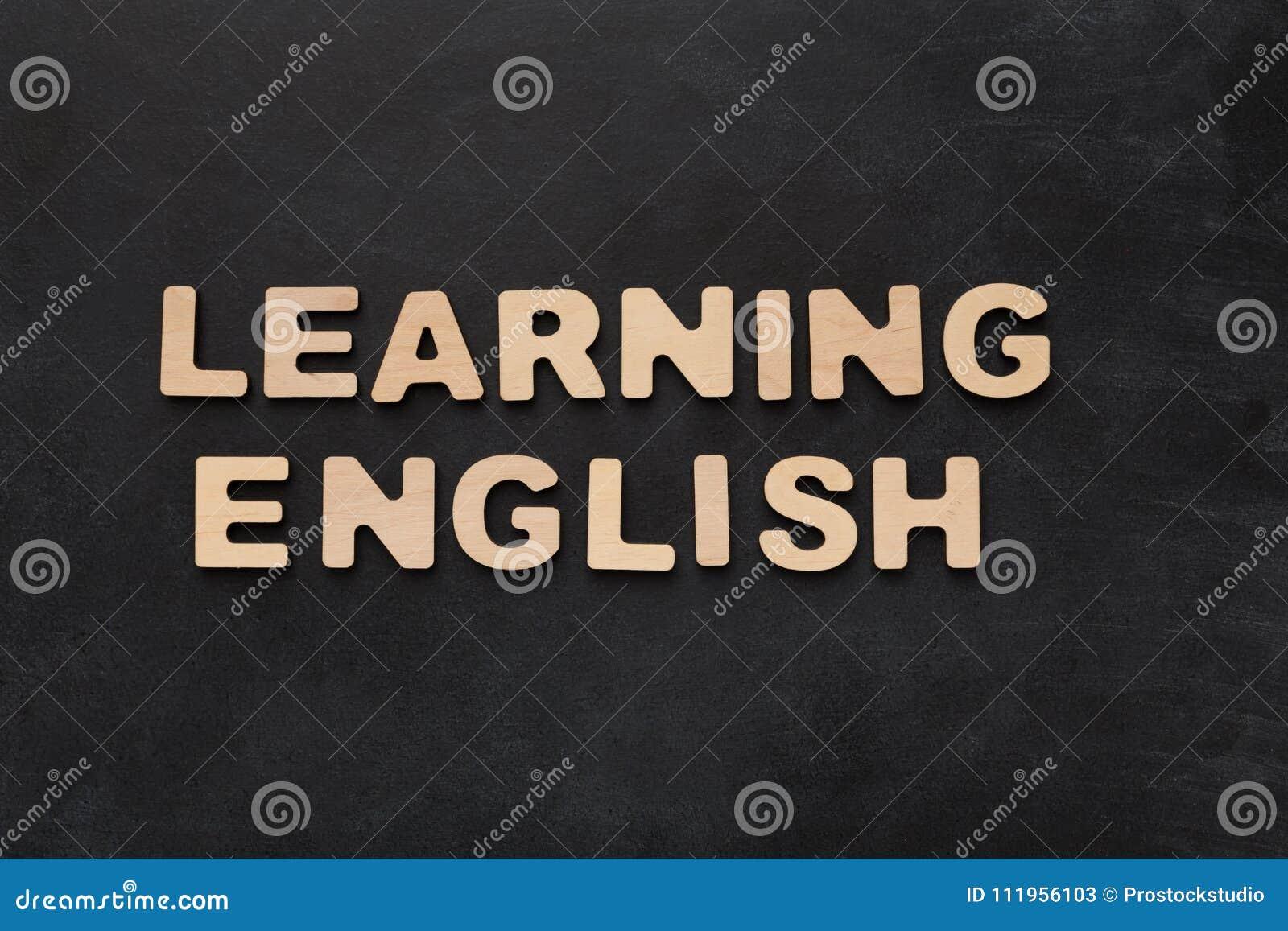Englisch lernend, buchstabierte mit hölzernen Buchstaben auf schwarzem Hintergrund