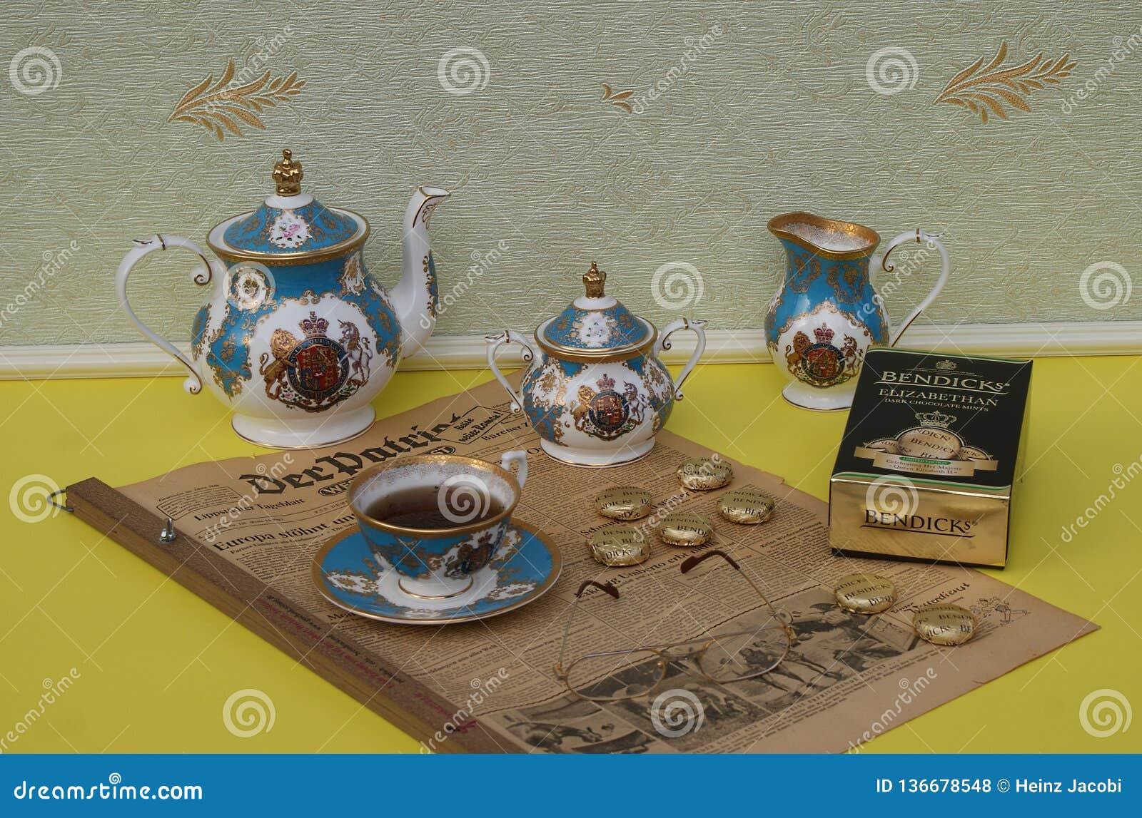 Englischer Teesatz, ein Paket von Bendicks elisabethanischen Schokoladenminzen und Lesebrille auf einem alten deutschen Zeitung D
