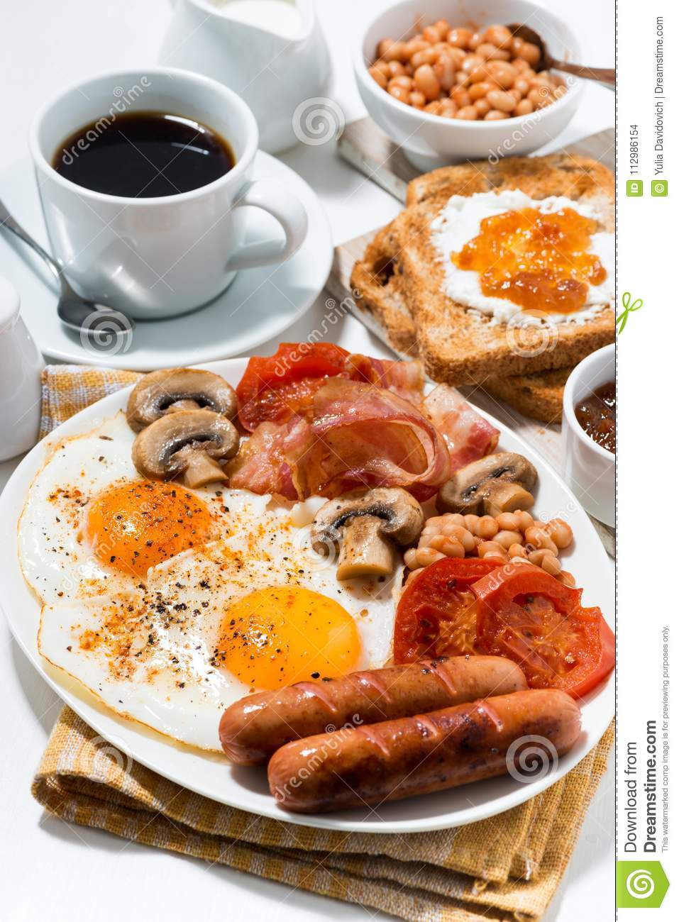 English breakfast of scrambled eggs with bacon, sausages