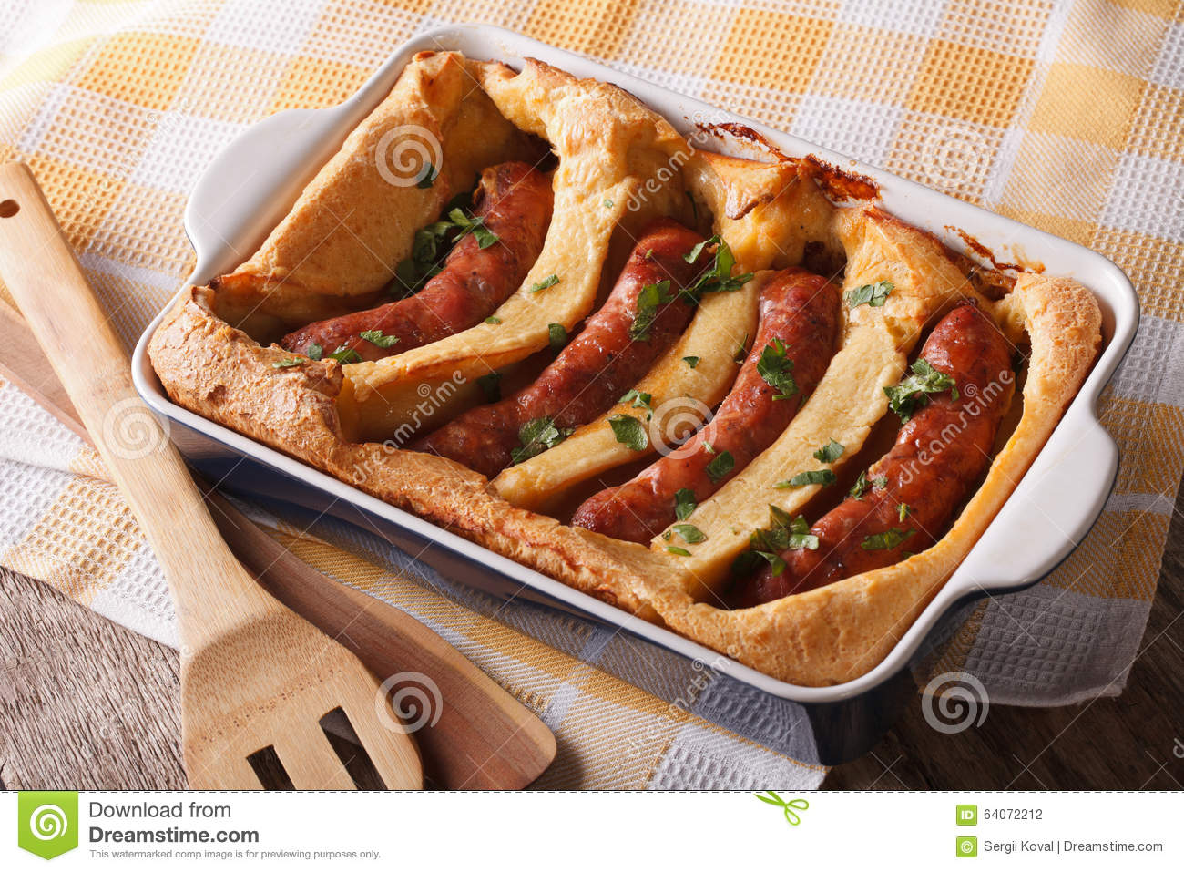 English food: toad in the hole into a baking dish close up. Horizontal