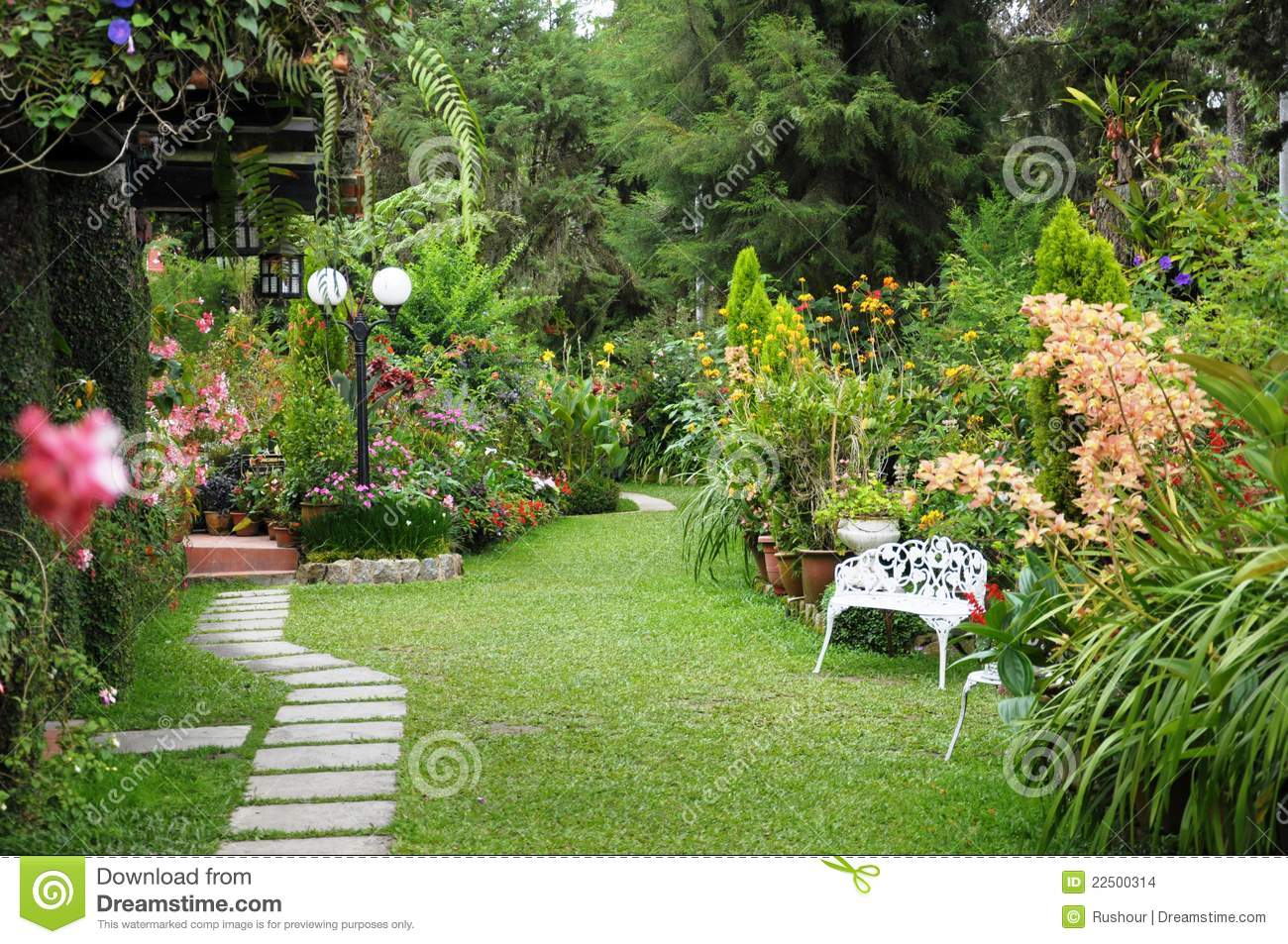 Beautiful english country garden featuring brick side walk white