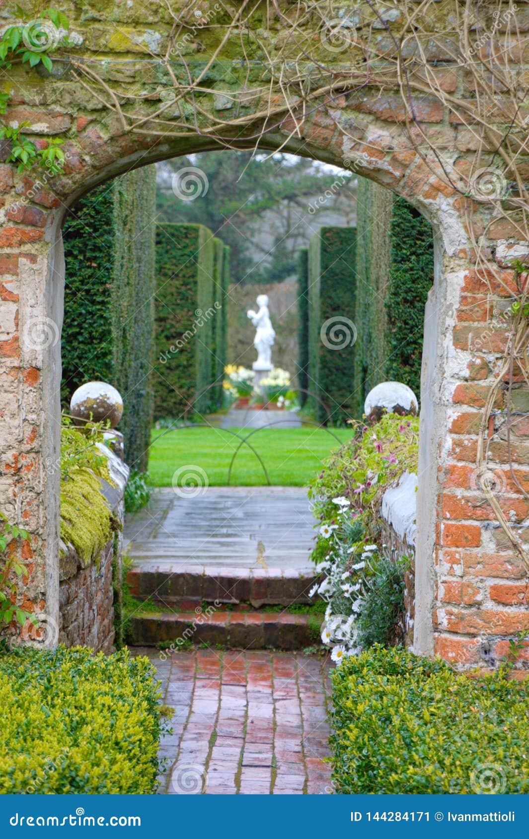 English Garden Gate With A Marmoreal Sculpture Between Shrubs Of