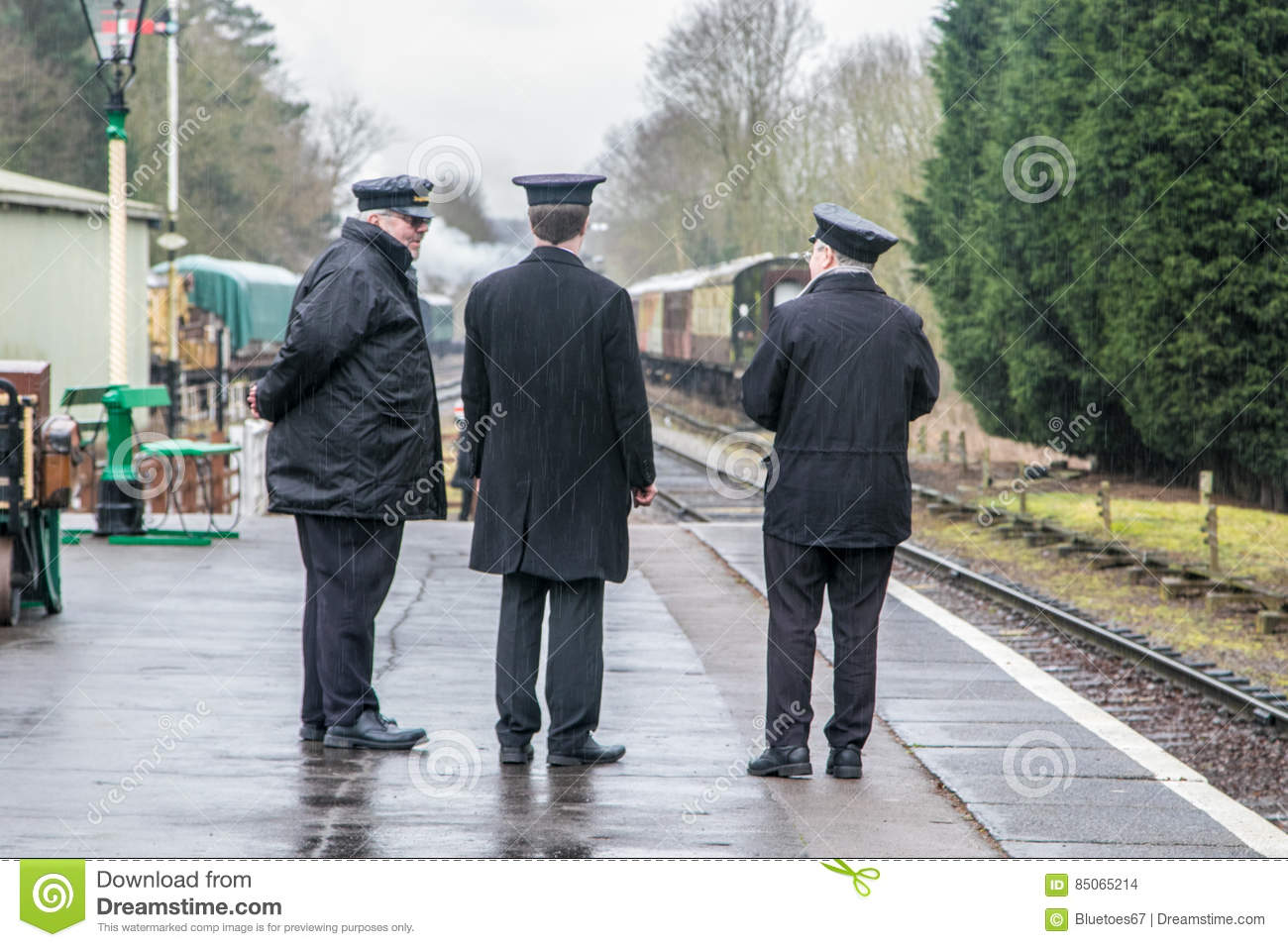 English steam trains and three conductors on the platform