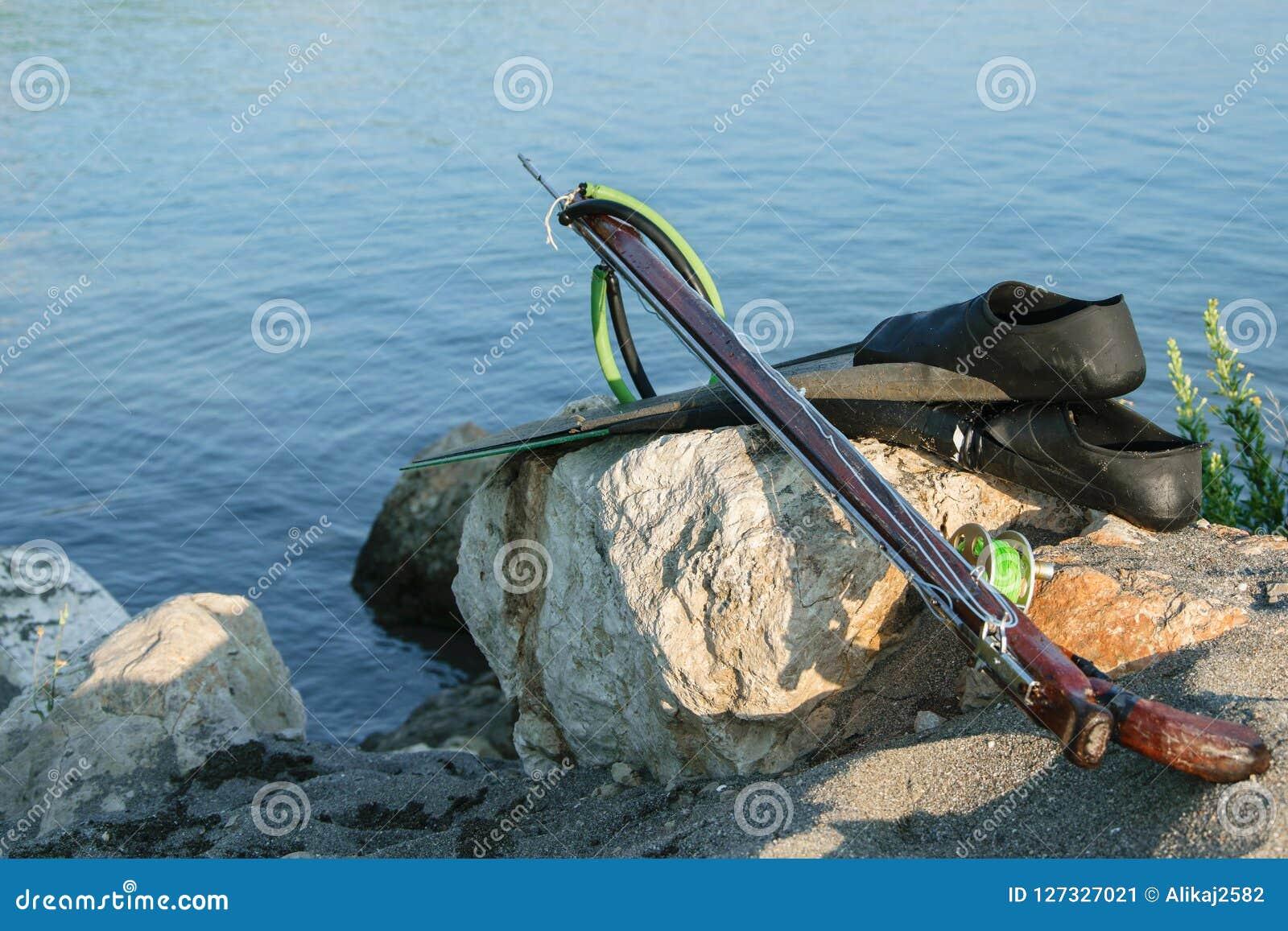 Engranaje de Spearfishing - aletas, speargun en una roca del mar contra s azul