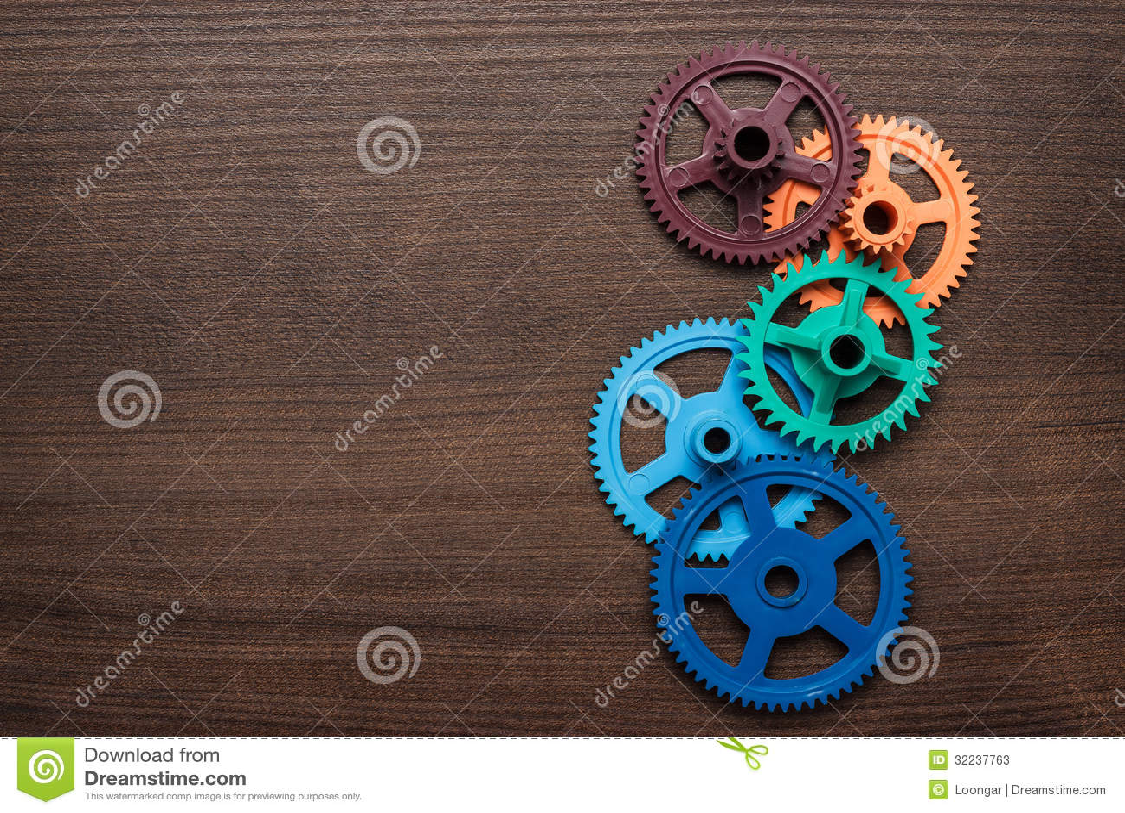 Engranajes coloridos en el fondo de madera