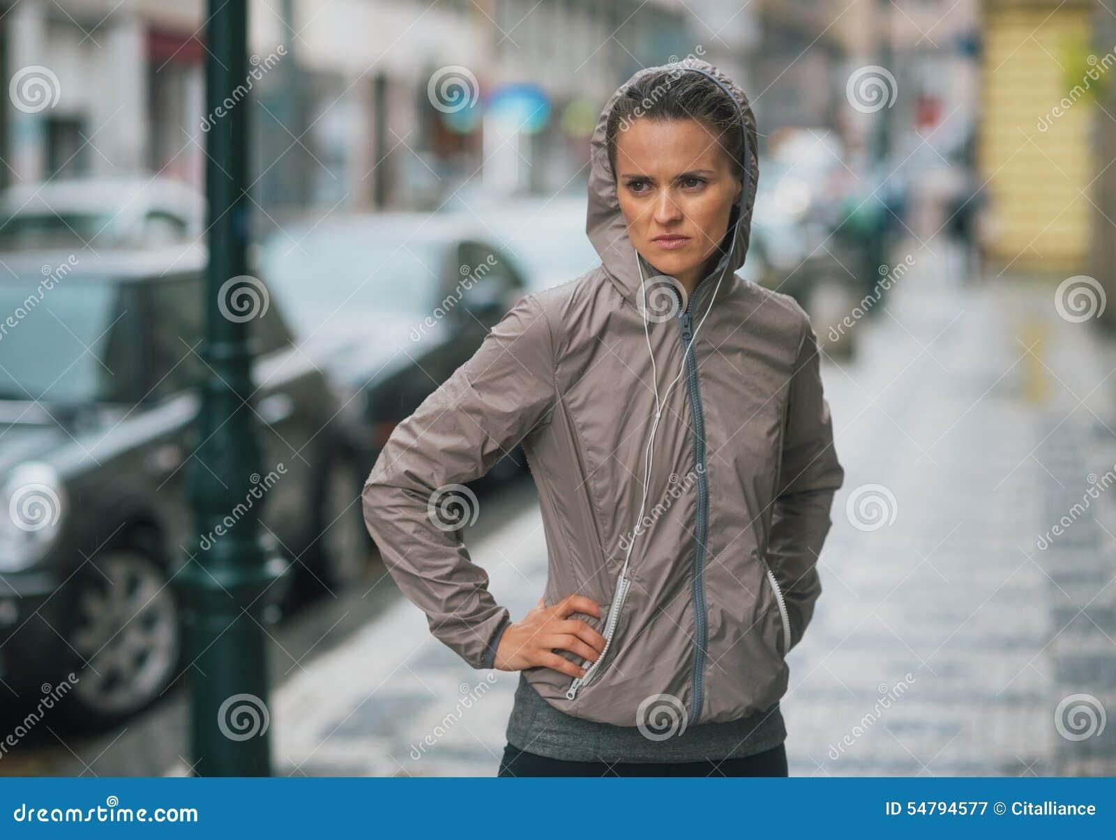 Engrenagem vestindo da chuva do corredor da mulher parada e que sente gratuito