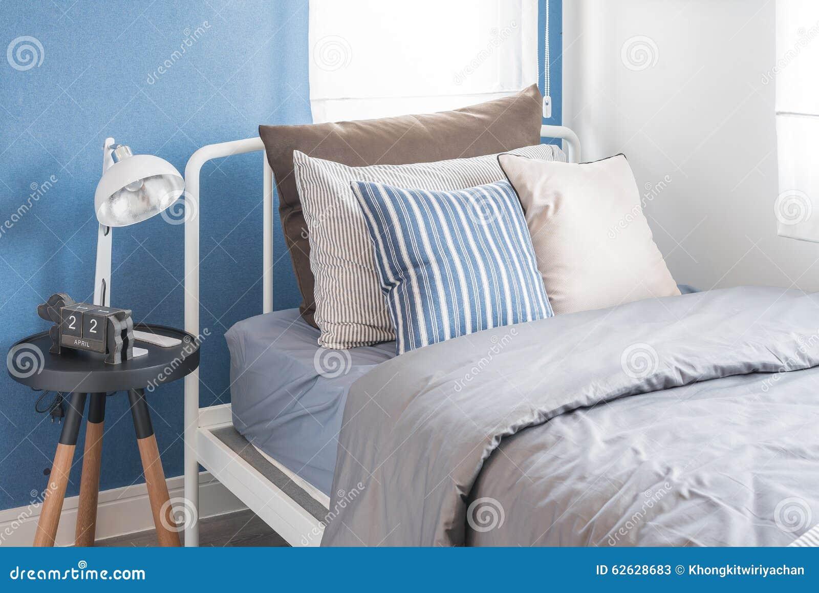 Blauwe Slaapkamer Lamp : Enig wit bed met witte lamp en blauwe muur stock afbeelding