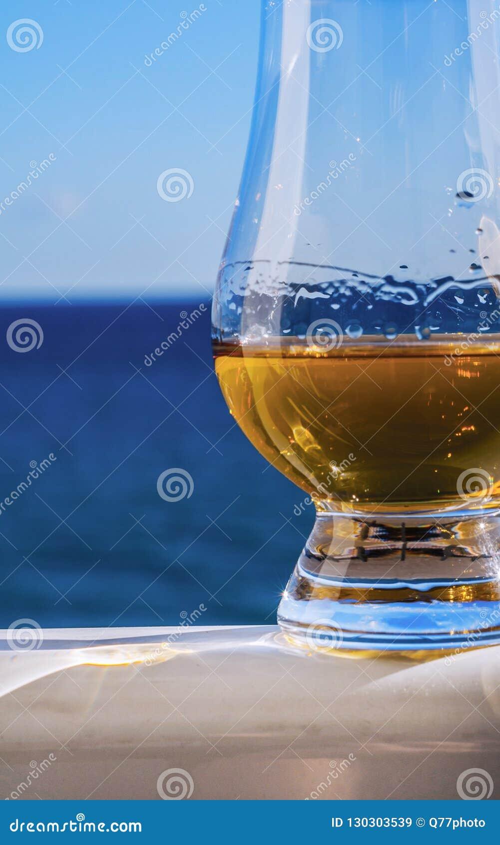 Enige moutwhisky in een glas van het proeven op de overzeese achtergrond,