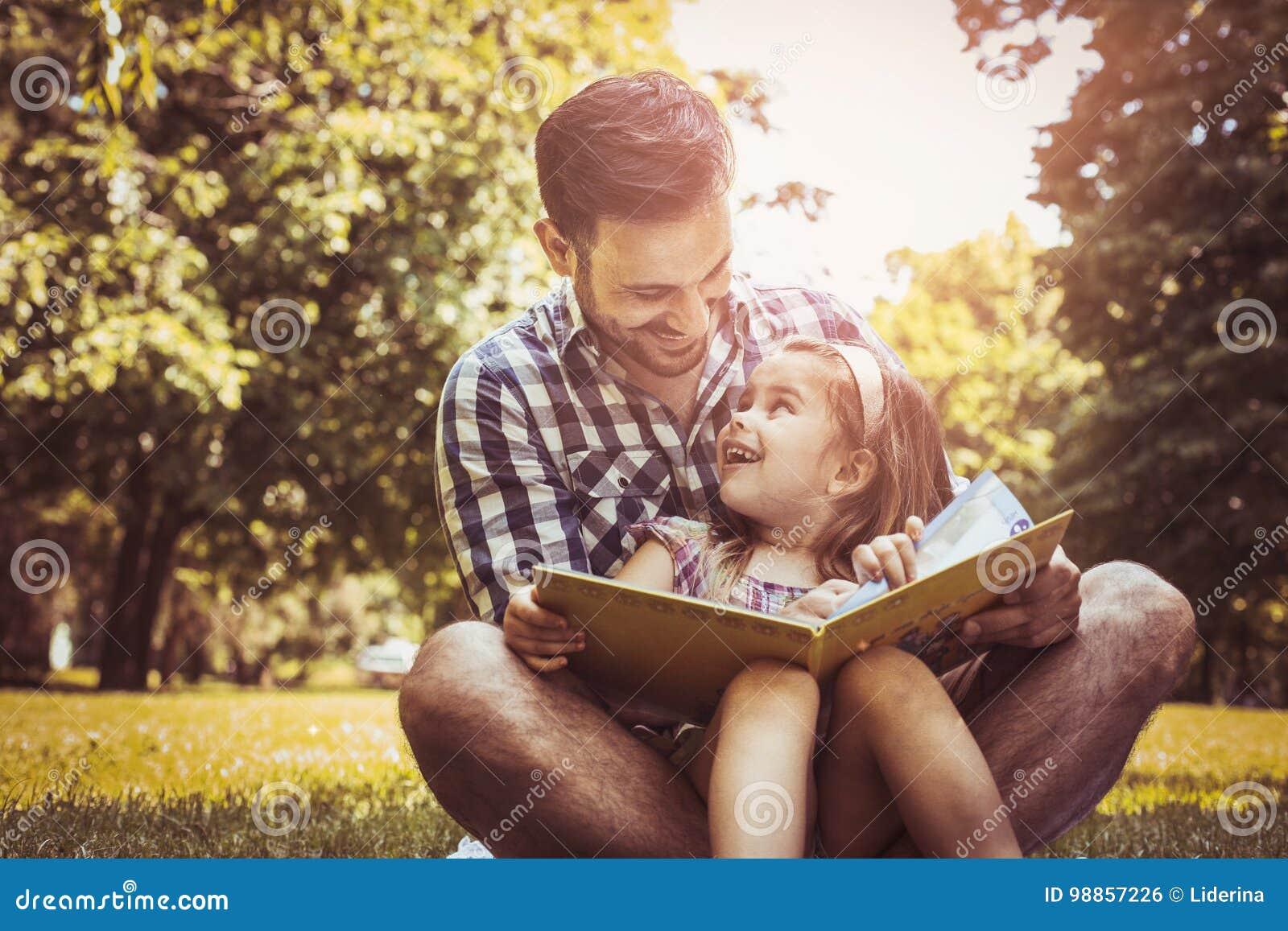 Enige vaderzitting op gras met weinig dochter