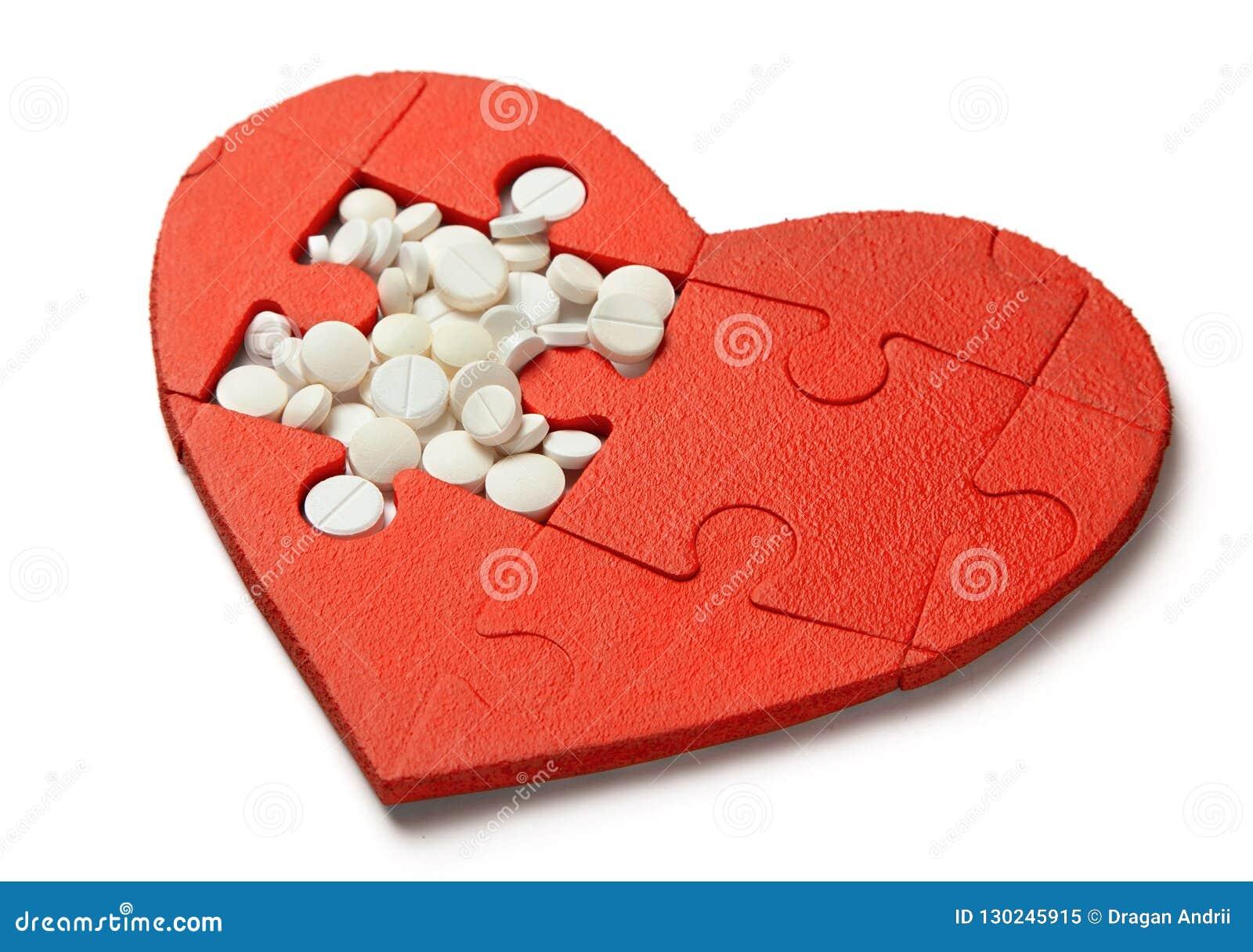 Enigma do coração vermelho e comprimidos brancos isolados no fundo branco Tratamento do conceito de comprimidos da doença cardíac