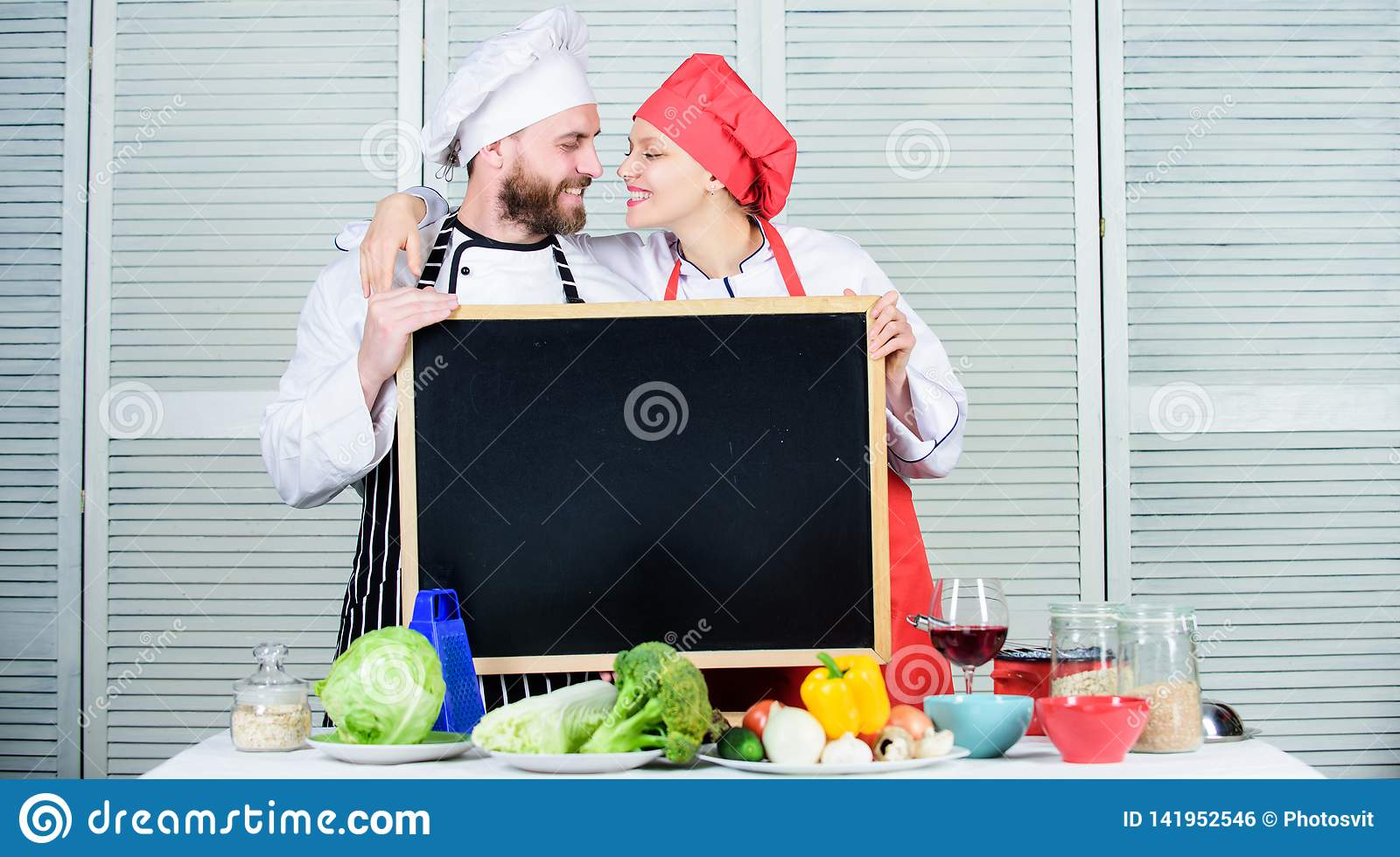 Enjoy the fun unfolding in the kitchen. Master cook and prep cook hugging in cooking school. Couple in love of man and
