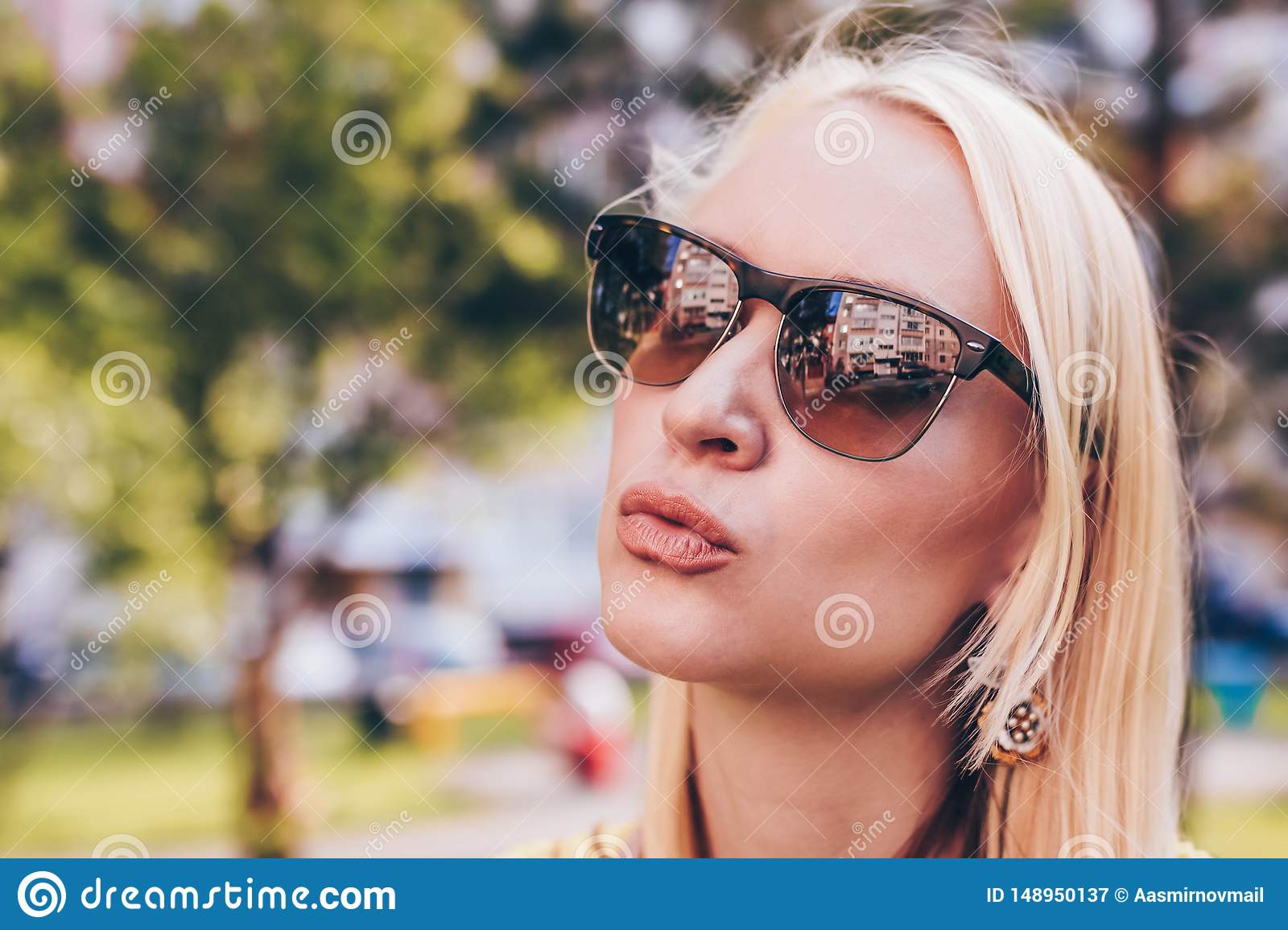 Beautiful blond woman in sun glasses give a kiss to you. Funny lifestile concept