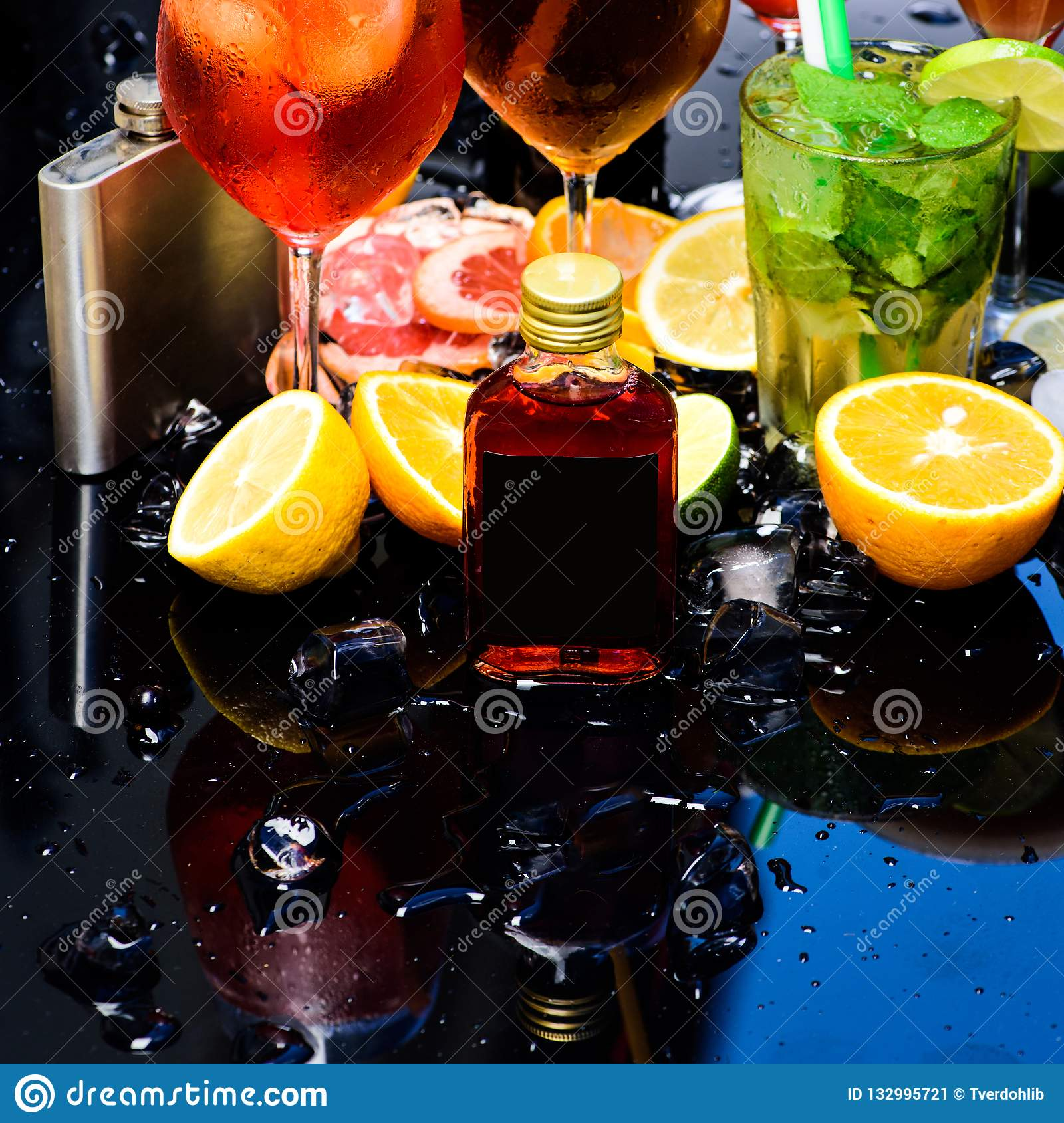 Enjoy a variety of specialty cocktails. Whiskey cocktail drinks in glasses. Cocktails garnished with ice cubes, fruit