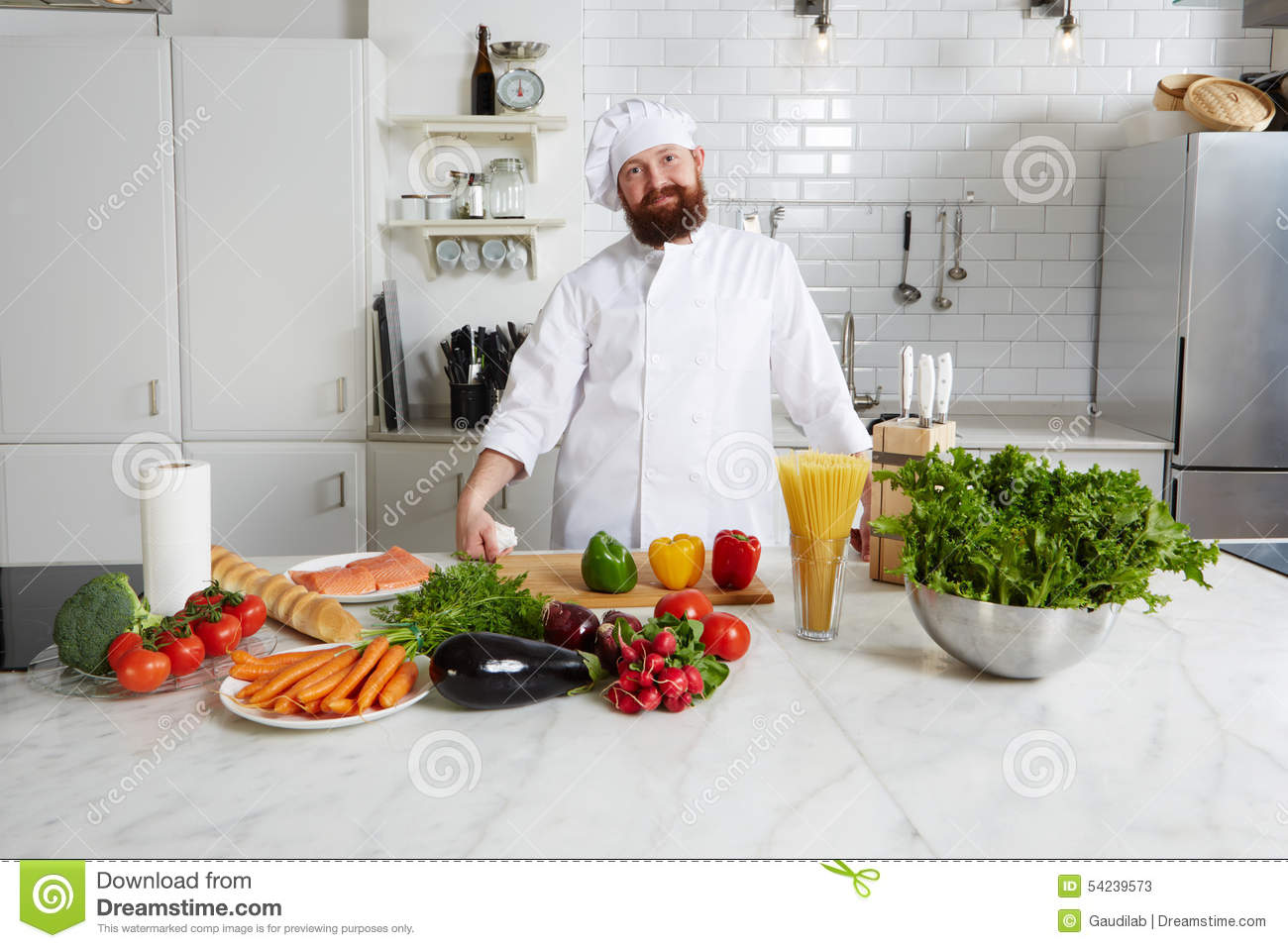 Enjoyable smiling chef with fresh vegetables on big table standing in the kitchen